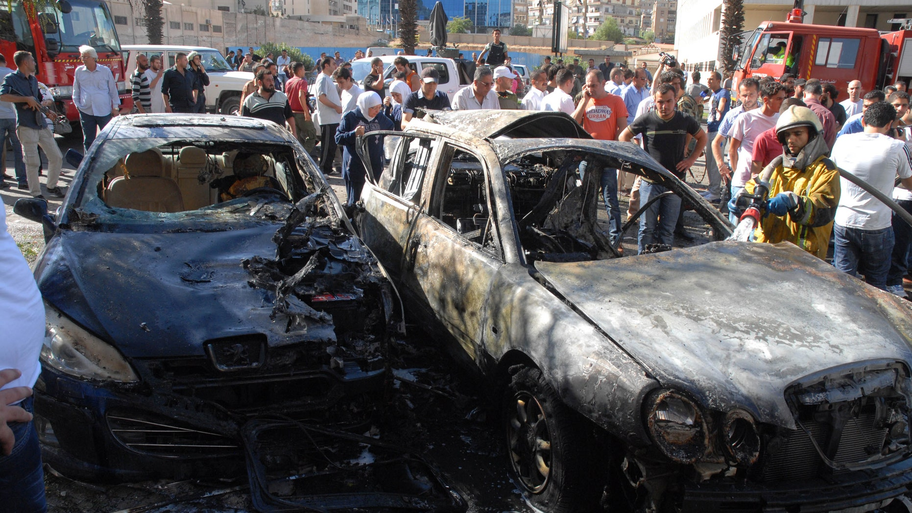 Sept. 7, 2012: In this photo released by Syria's state-run news agency, SANA, a firefighter extinguishes a burned car close to where an explosion went off between the buildings of the Ministry of Information and the Ministry of Justice, which are about 100 yards apart, in Damascus, Syria.