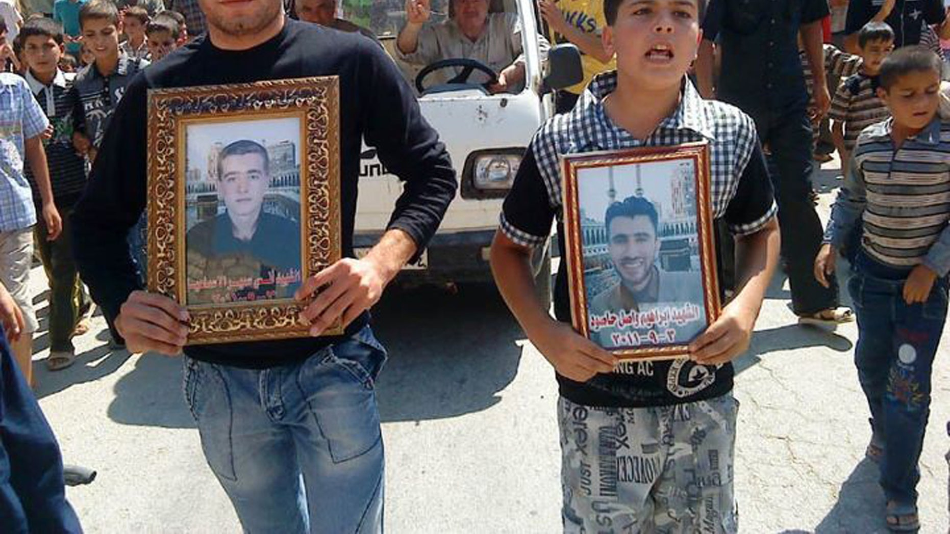 Anti-Syrian President Bashar Assad protesters hold portraits for their dead relatives killed in recent violence, as they march during a demonstration against the Syrian regime, at Maaret Harma village, in Edlib province, Syria, on Friday Sept. 9, 2011.