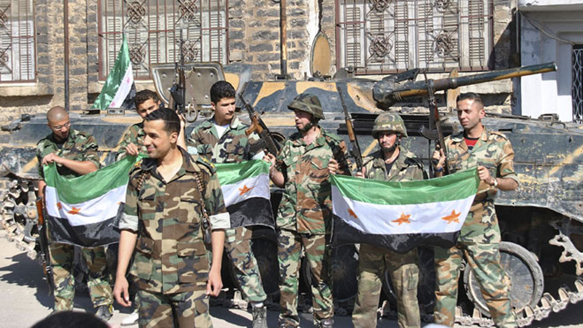 May 12, 2012: Syrian army soldiers hold the Syrian revolution flags as they stand in front their armored personnel carrier shortly after they defected and joined the rebels at Khaldiyeh neighborhood, in Homs province, central Syria.