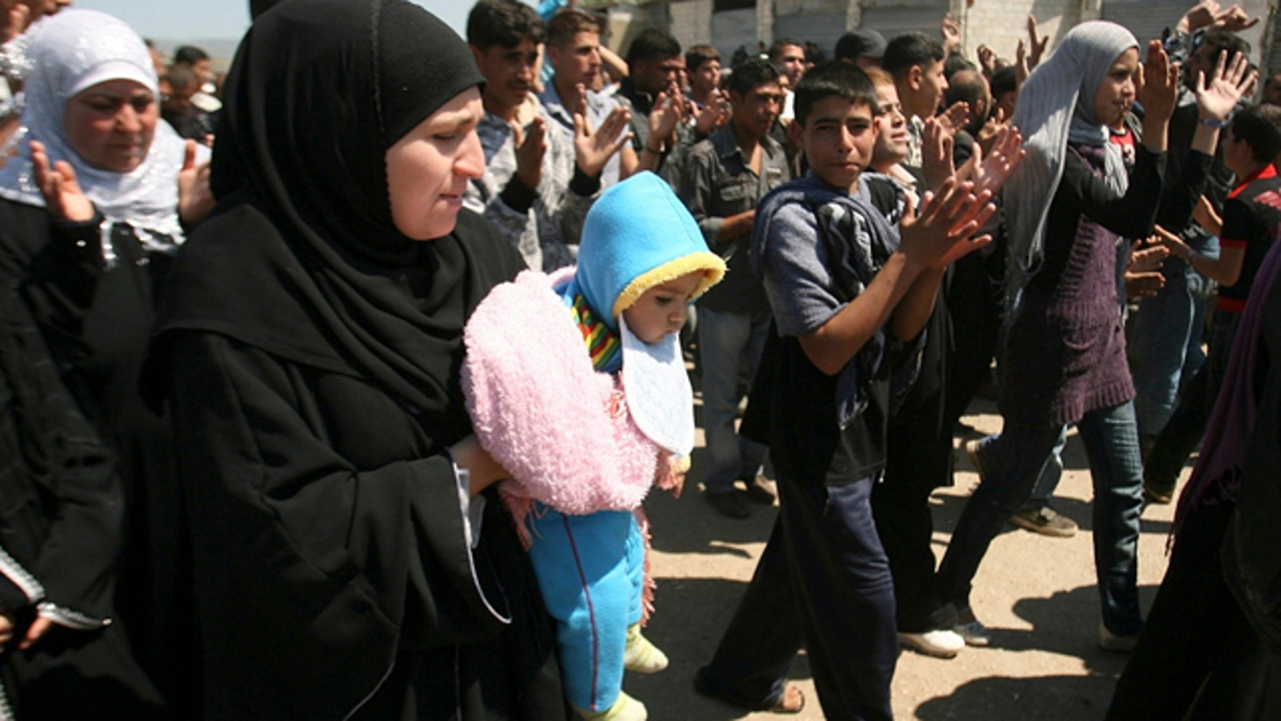 May 16: Syrian citizens who fled from violence from the western Syrian villages along the Lebanese-Syrian border, protest as they shout slogans against Bashar Assad and his regime. Carrying mattresses and bags of clothing, Syrians fleeing their homeland described a 'catastrophic' scene Monday in a besieged border town that has been largely sealed off as the army tries to crush a two-month uprising.