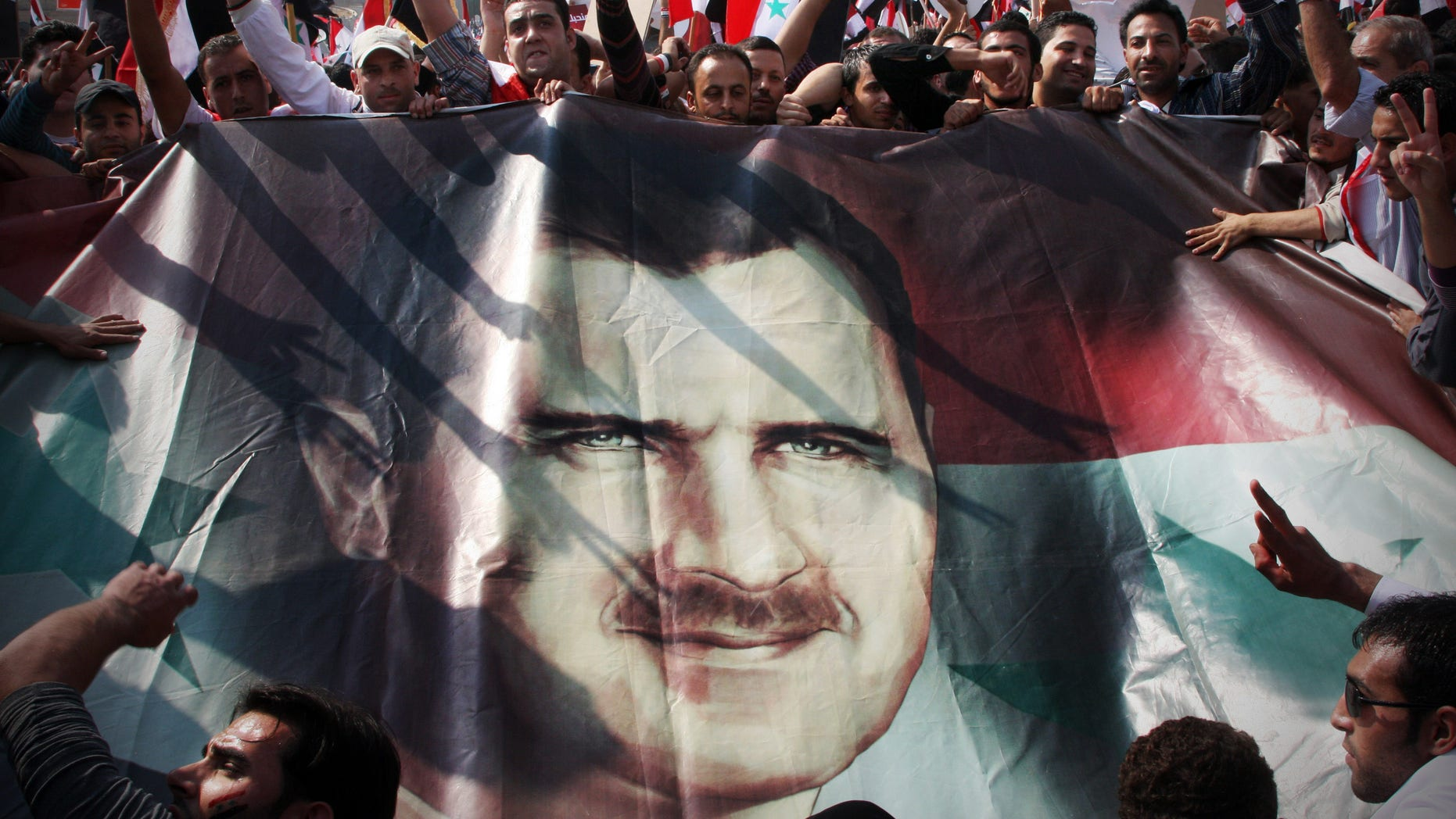 Oct. 26, 2011: Syrian regime supporters flash the V-victory sign as they hold up a portrait of Syrian President Bashar Assad during a rally at Umayyad Square in Damascus, Syria.