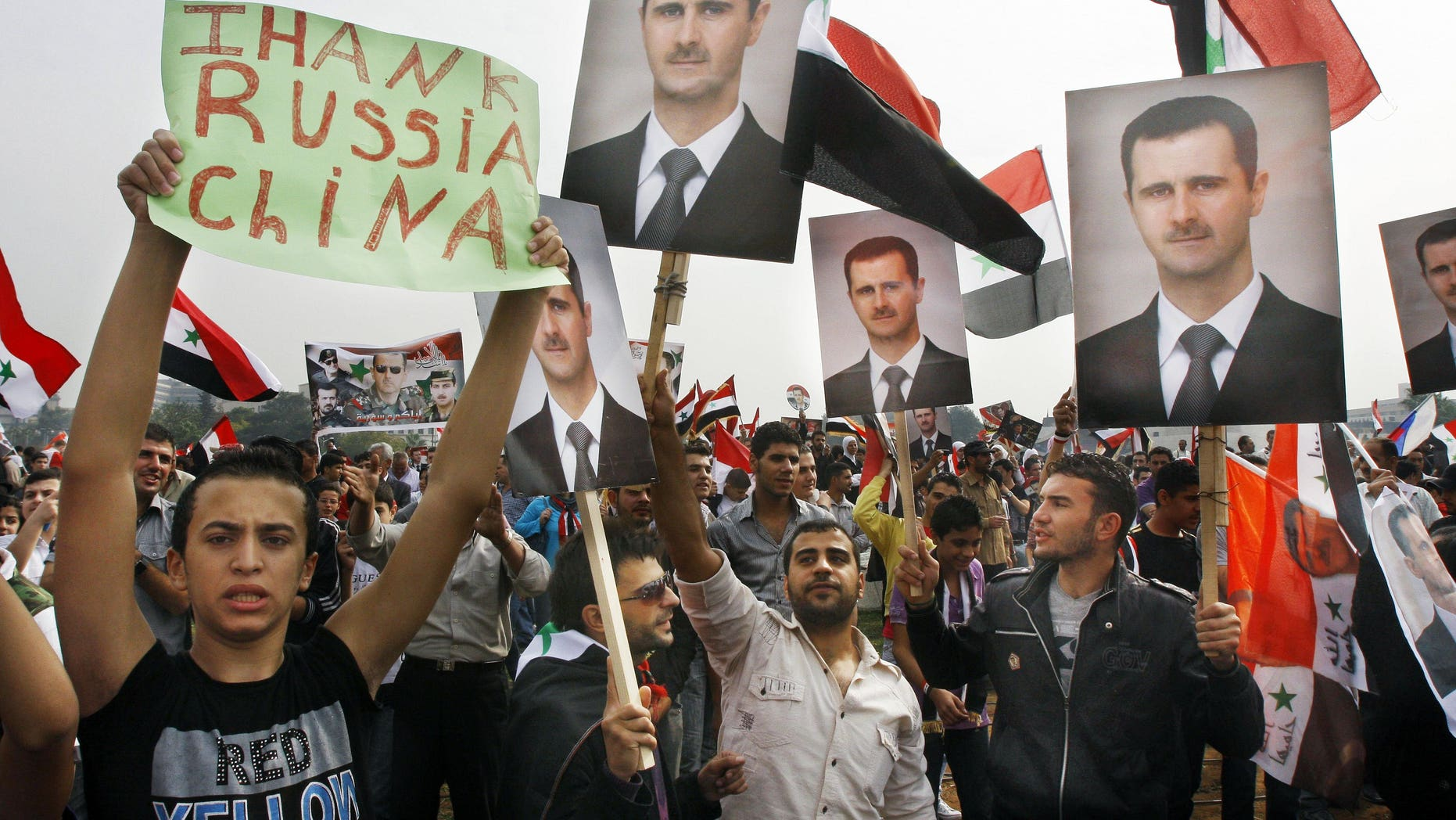 "Oct. 26, 2011: Syrian regime supporters hold up Bashar Assad's portrait and a man holds up a banner that reads ""Thank China and Russia"" during a rally in Umayyad Square in downtown Damascus, Syria."