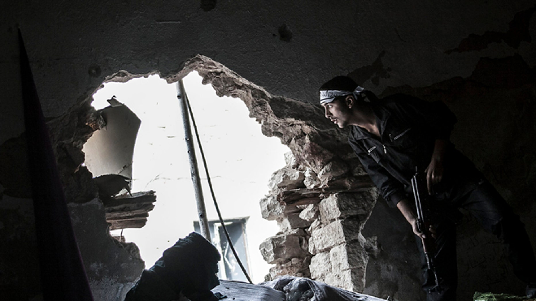 Oct. 24, 2012 photo: A Free Syrian Army fighter watches over an enemy position as rebel fighters belonging to the Liwa Al Tawhid group carry out a military operation at the Moaskar front line, one of the battlefields in the Karmal Jabl neighborhood, in Aleppo, Syria.