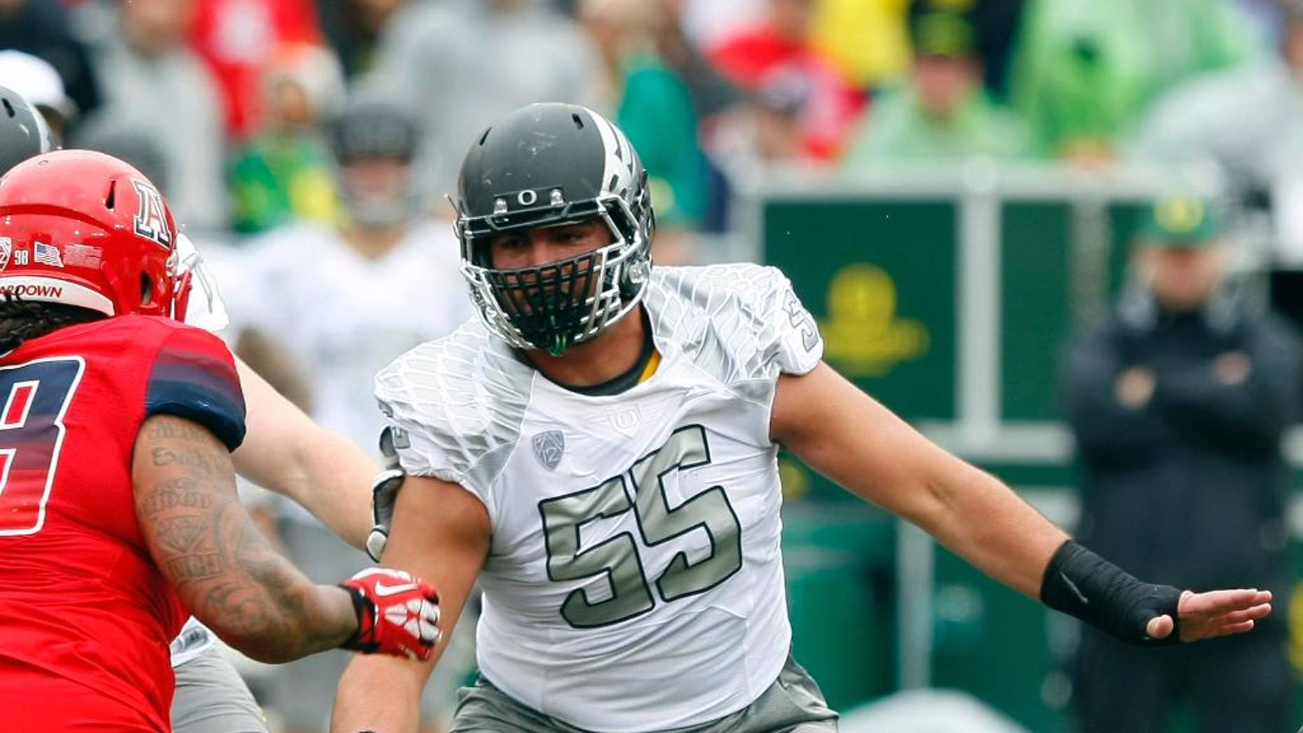 """This photo taken Nov. 23, 2013, shows Oregon offensive linesman Hroniss Grasu (55) during the first half of an NCAA football game against Arizona, in Tucson, Ariz. Grasu never would have played football if his parents had their way. Steve and Mariana Grasu, immigrants from Romania, preferred soccer over American football, which that saw as too violent. It was only reluctantly that he was allowed to kick for his high school team, and when a coach put him on the offensive line, well, he didn't exactly mention it to his folks. It was a long, silent ride home when the Grasus attended their son's first game. """"They enjoy it now. They come to every single game, home and away,'' he laughs.(AP Photo/Rick Scuteri)"""