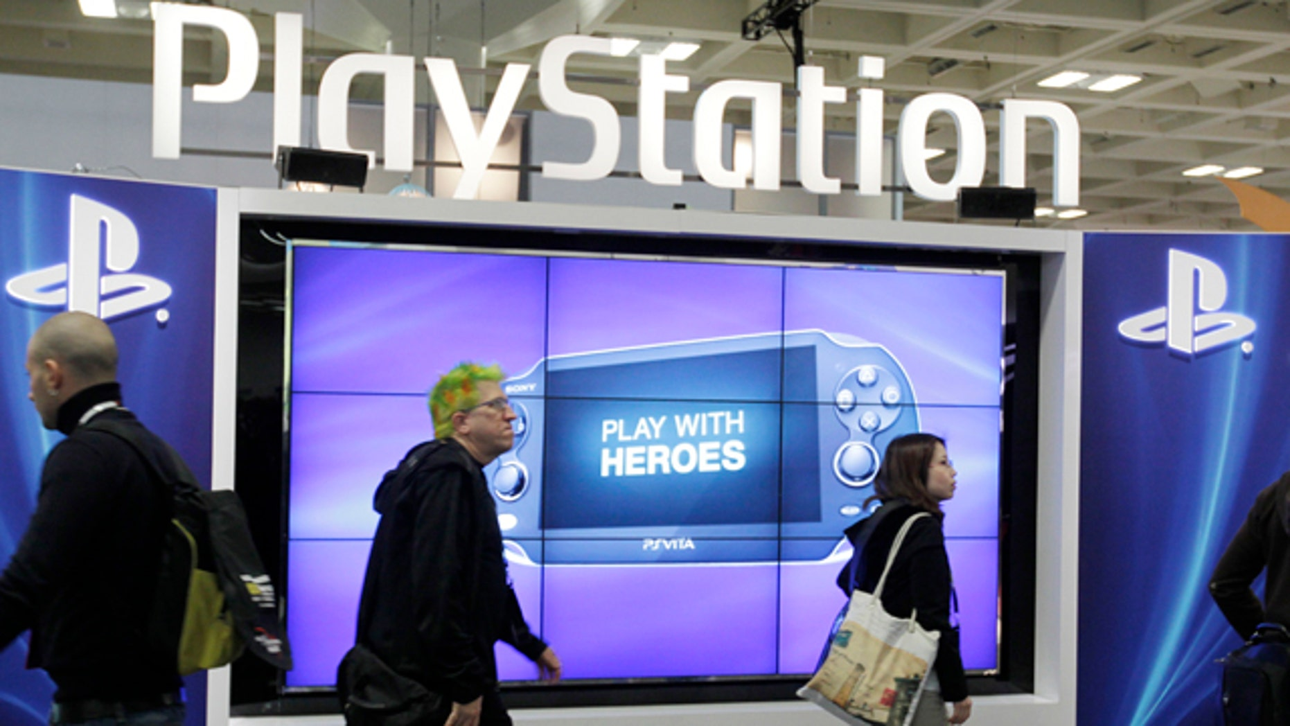 FILE- This March 8, 2012 file photo shows attendees walking past the Sony PlayStation PS Vita console on display in the Sony PlayStation booth at the Game Developers Conference in San Francisco. (AP Photo/Paul Sakuma, File)