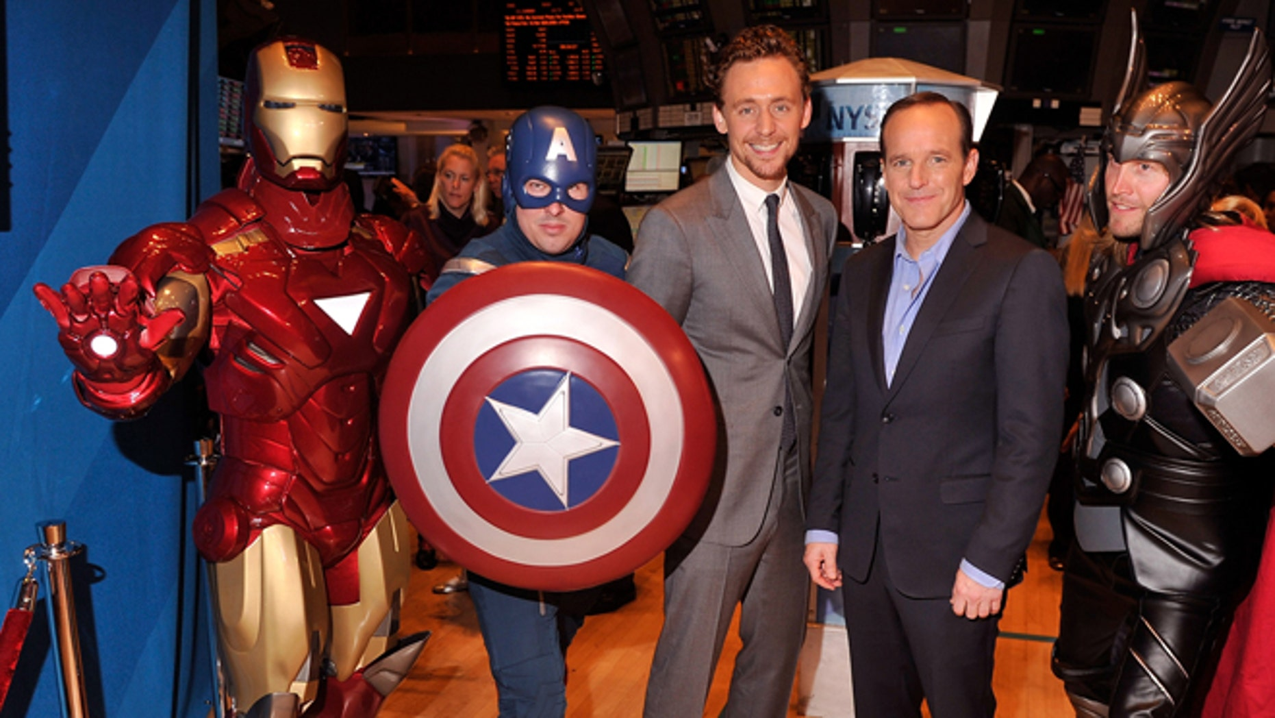 """May 1, 2012: Actors Tom Hiddleston (third from left) and Clark Gregg (second from right) pose for a photo aa celebration of the release of Marvel Studios  """"The Avengers"""" after ringing the opening bell at the New York Stock Exchange in New York City."""