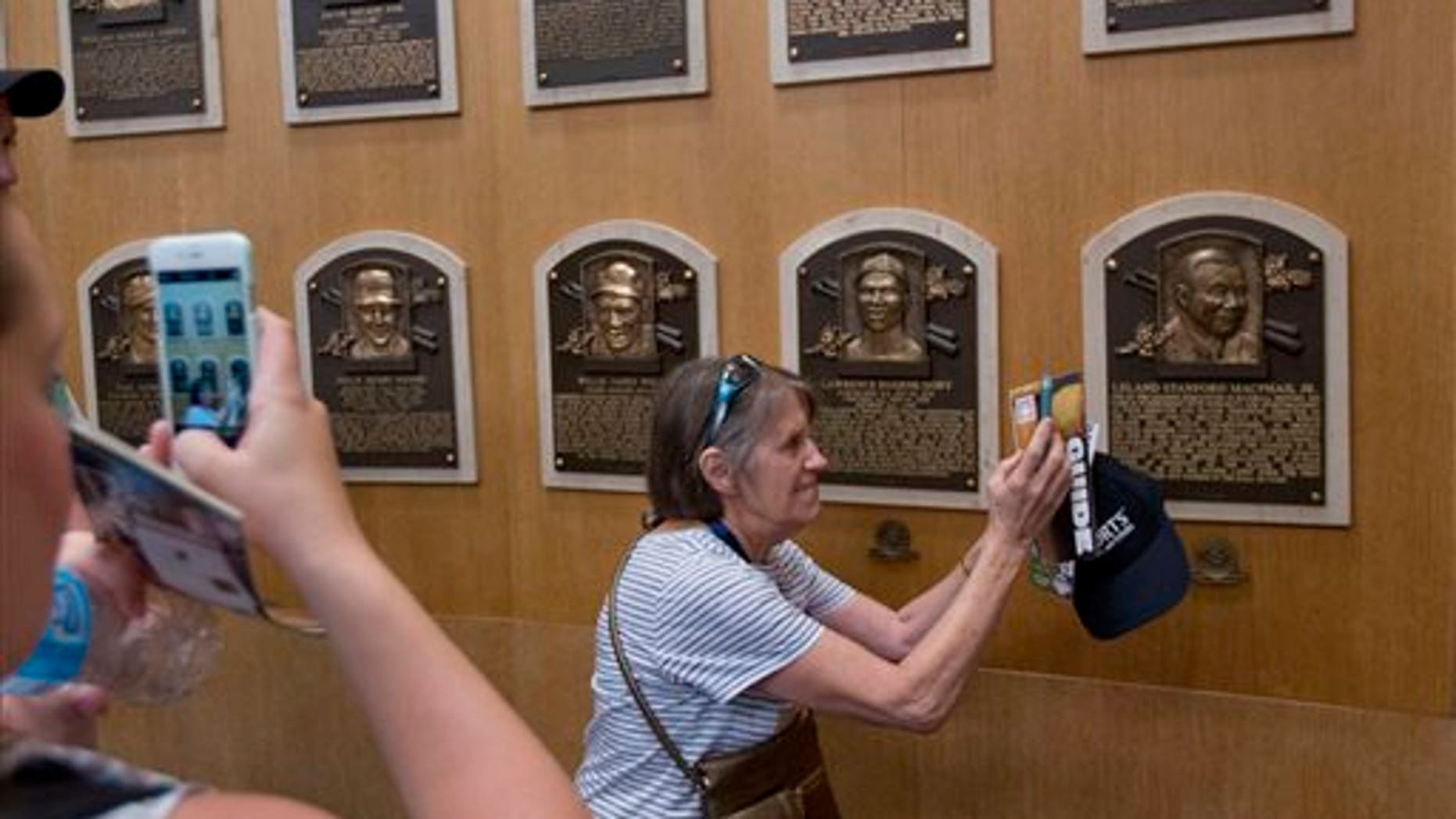Fans visit the Plaque Gallery at the National Baseball Hall of Fame on Saturday, July 25, 2015, in Cooperstown, N.Y. Former Major League Baseball players Pedro Martinez, Randy Johnson, Craig Biggio and John Smoltz will be inducted to the hall on Sunday. (AP Photo/Mike Groll)