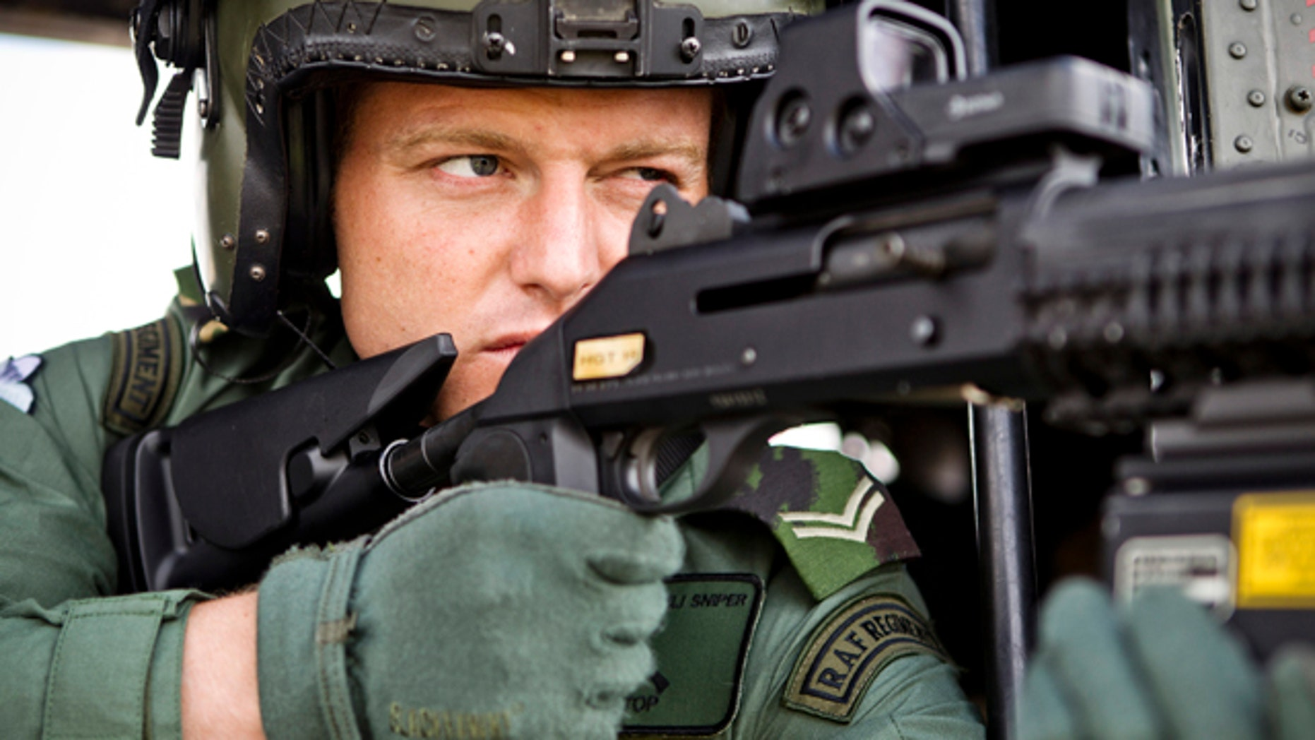 July 13, 2012: In this photo released by the British MOD, a sniper with Royal Air Force Regiment Sniper, sights through his scope from inside an RAF Puma helicopter at RAF Northolt ahead of carrying out air security duties for Op Olympic, in London.