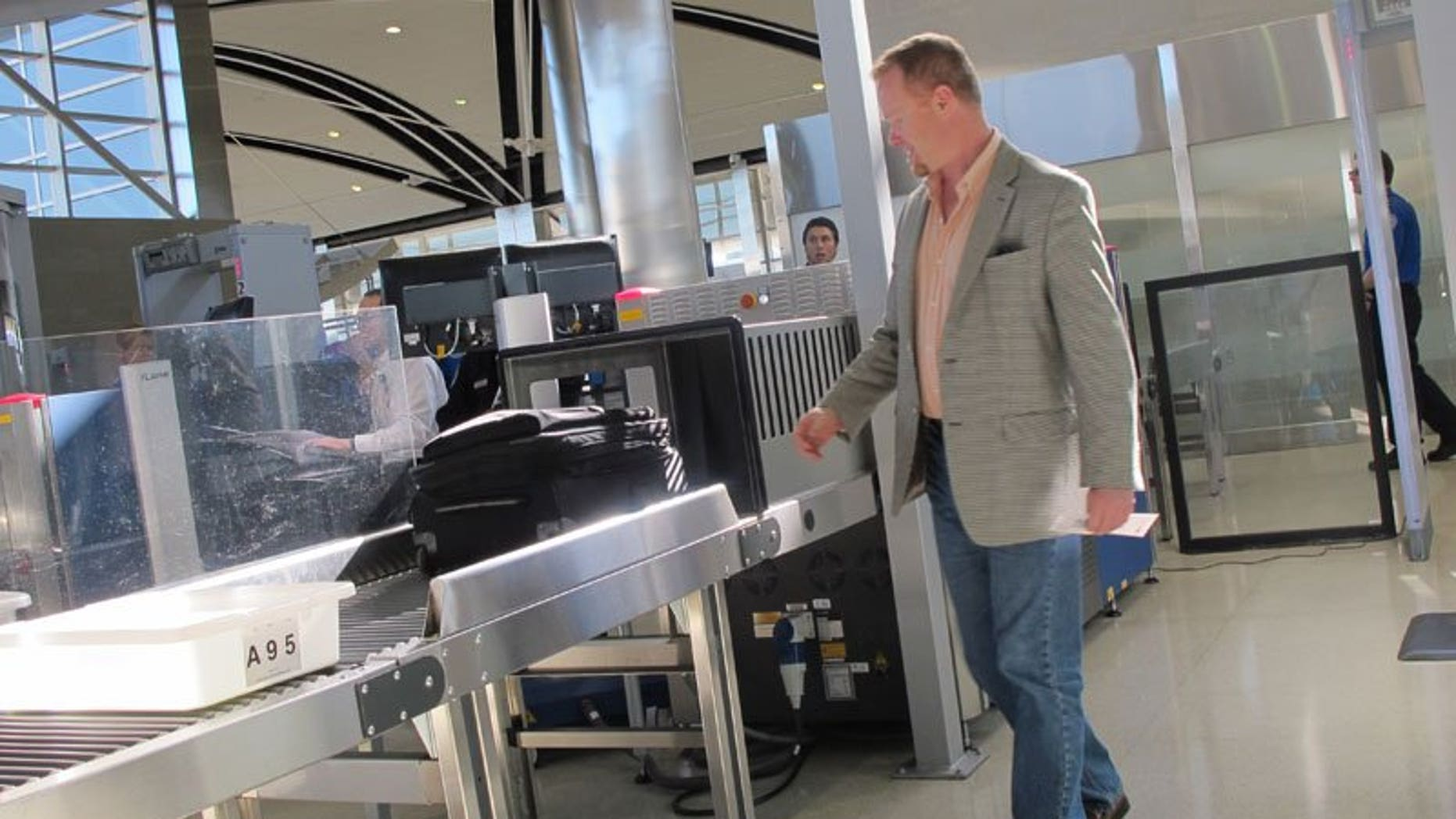 October 4: Mark Daly of Novi, Michigan, passes through the new expedited screening line at Detroit Metro Airport in its first hours of operation.