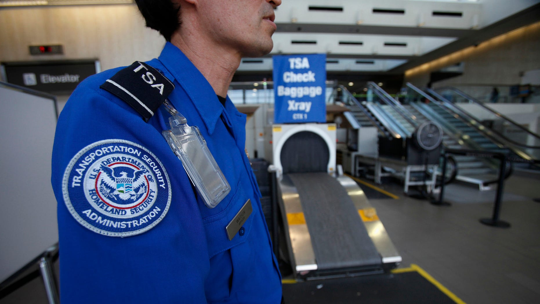 FILE: March 4, 2013: A Transportation Security Administration officer waits by an X-ray machine at Los Angeles International Airport in Los Angeles, Calif.