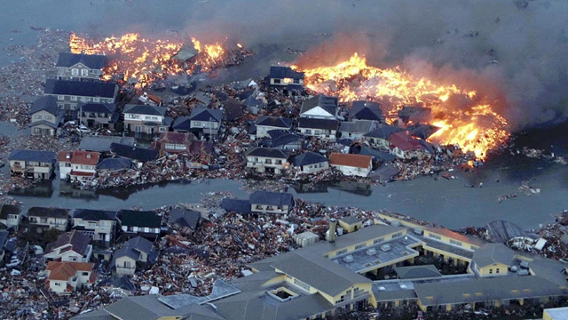 March 11: Houses are in flame while the Natori river is flooded over the surrounding area by tsunami tidal waves in Natori city, Miyagi Prefecture.