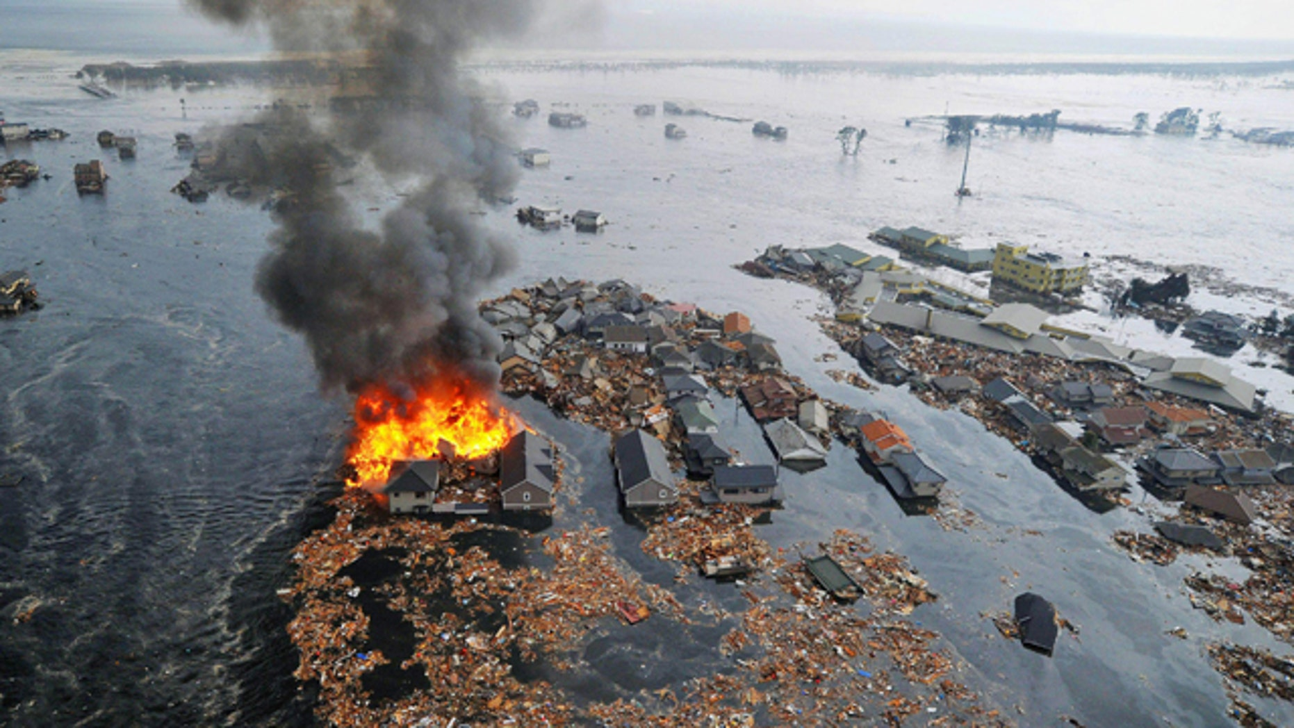 March 11: Houses swallowed by tsunami waves burn in Sendai, Miyagi Prefecture (state) after Japan was struck by a strong earthquake off its northeastern coast.