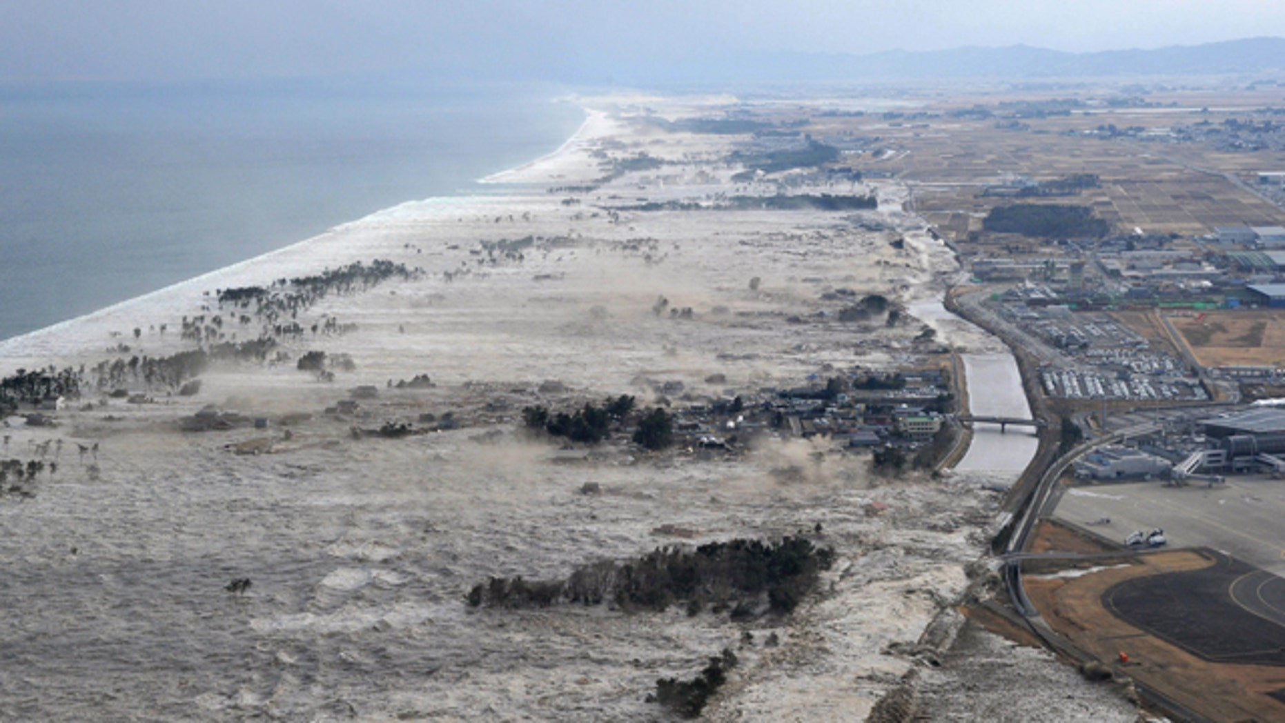 March 11: Earthquake-triggered tsumanis sweep shores along Iwanuma in northern Japan.