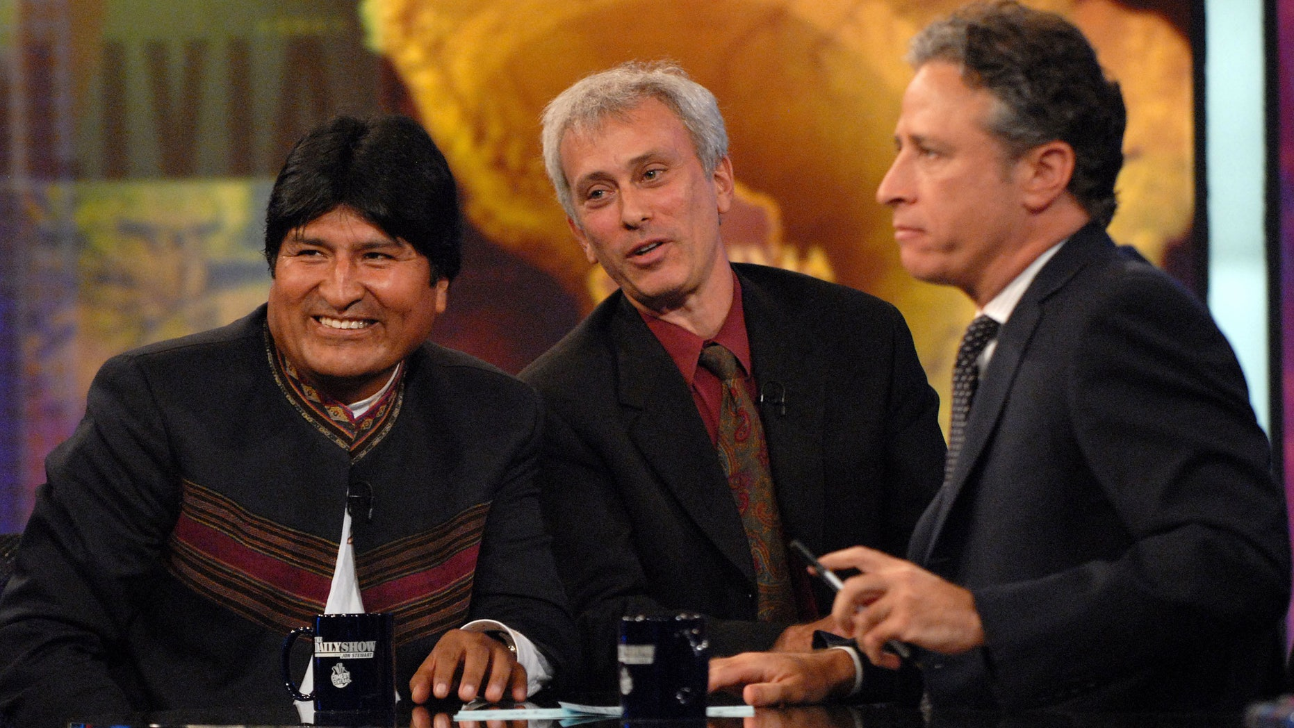 """FILE - In this Sept. 25, 2007 file photo, Bolivian President Evo Morales, left, speaks with host Jon Stewart, right,  as an interpreter looks on, during a taping of Comedy Central's """"The Daily Show with Jon Stewart"""" in New York. Morales, a poor farmer, became the country's first indigenous president and assumed office in 2006. After more than 16 years and nearly 2,600 telecasts, Stewart will end his show on Aug. 6.  (AP Photo/Peter Kramer, FIle)"""