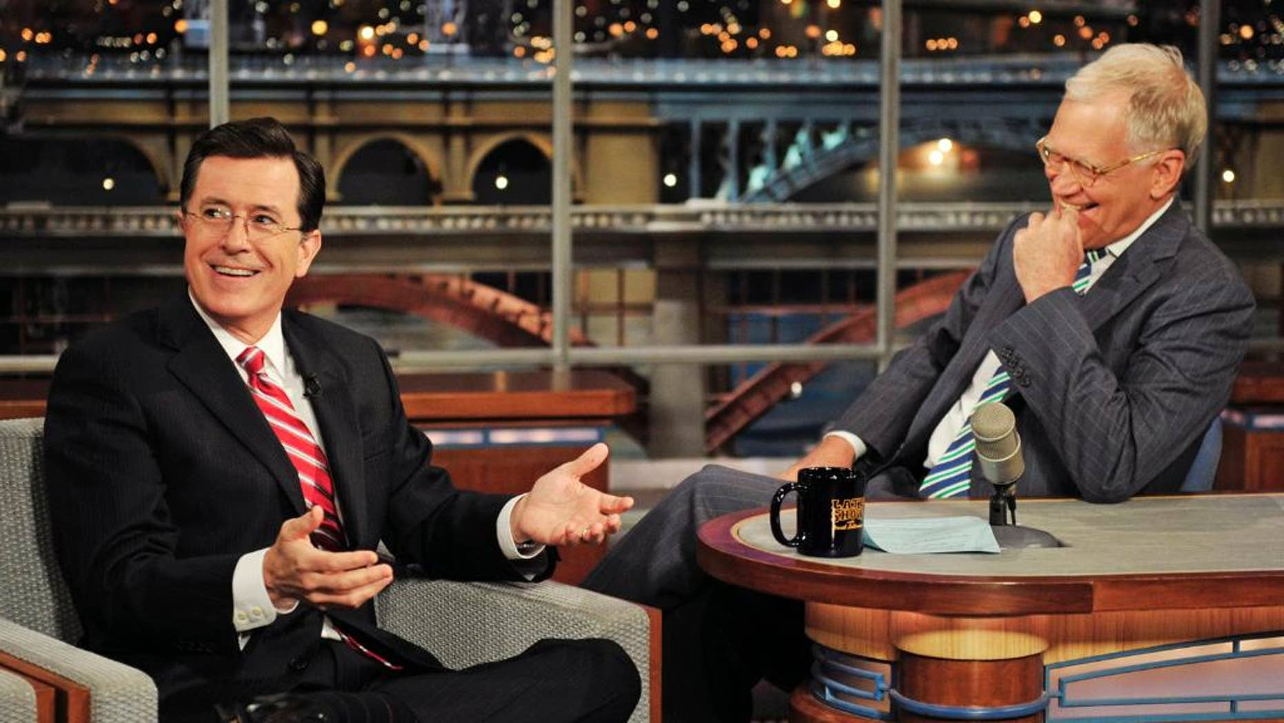 """In this May 3, 2012 photo provided by CBS, Stephen Colbert, left, host of the """"Colbert Report"""" on the Comedy Central Network, has a laugh on stage with host David Letterman on the set of the """"Late Show with David Letterman,"""" in New York. Colbert says on a visit to the late-night show he'll take over next year he's obviously """"thrilled"""" to be succeeding David Letterman. The Comedy Central host told Letterman on CBS' """"Late Show"""" on Tuesday, April 22, 2014, he's going to do whatever Letterman has done.  (AP Photo/CBS, John Paul Filo) MANDATORY CREDIT, NO SALES, NO ARCHIVE, FOR NORTH AMERICAN USE ONLY"""