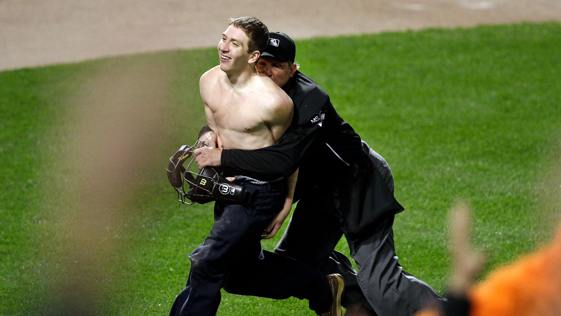 Umpire Jeff Kellogg, right, tackles a fan who ran onto the field in the middle of the seventh inning of a baseball game between the Oakland Athletics and the Baltimore Orioles in Baltimore, Friday, April 27, 2012. (AP Photo/Patrick Semansky)