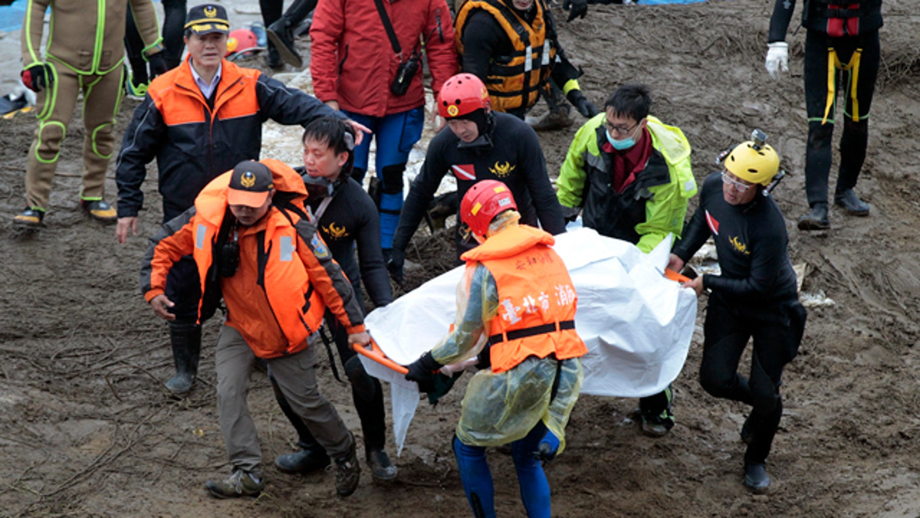 Feb. 6, 2015: Search and rescue divers carry a recovered body at the site of a commercial plane crash in Taipei, Taiwan. TransAsia Airways Flight 235 with 58 people aboard clipped a bridge shortly after takeoff and crashed into a river in the island's capital of Taipei on Wednesday morning. (AP Photo/Wally Santana)
