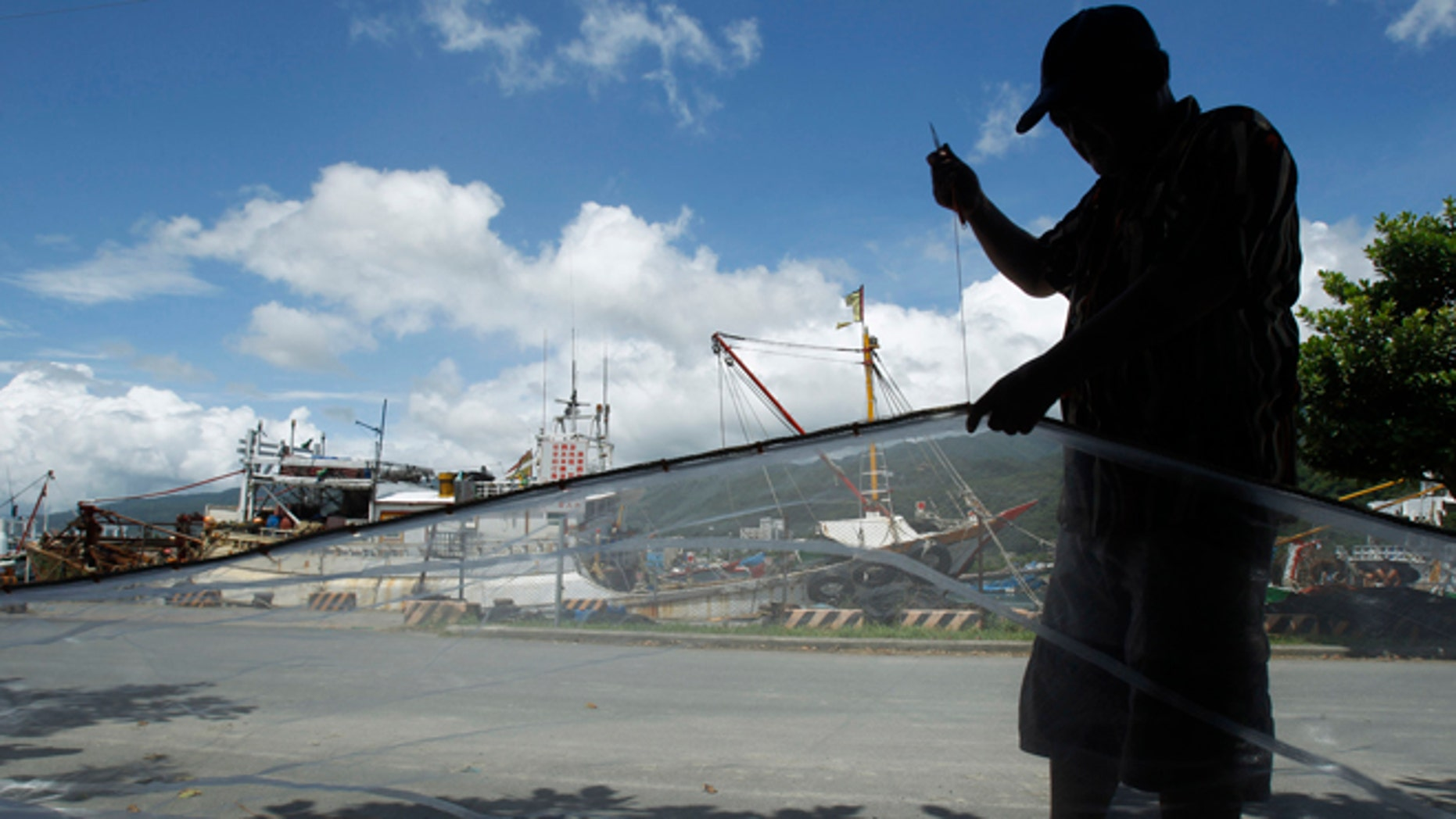 August 23, 2012: A fisherman repairs his nets at the dock as he waits out approaching Typhoon Tembin in the coastal village of Ilan, Taiwan.