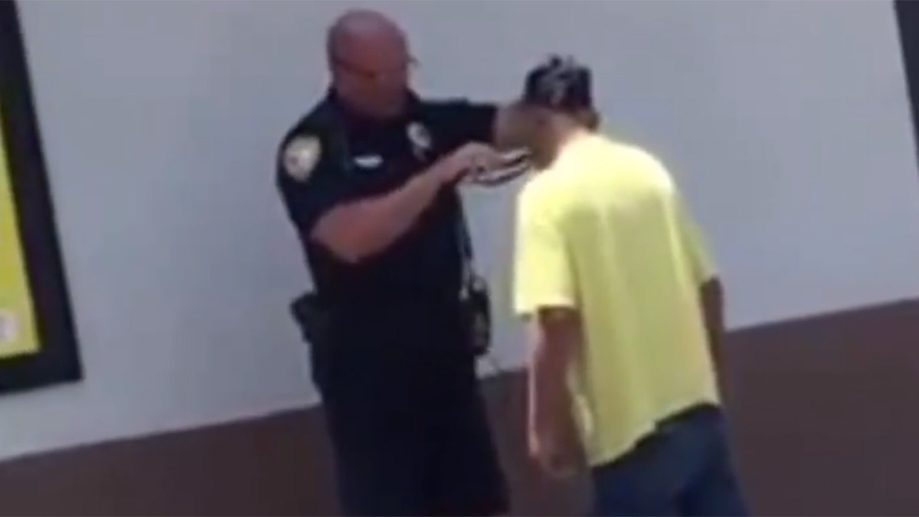 A Florida police officer went viral after being recorded helping a homeless man shave for a job interview at McDonald's.
