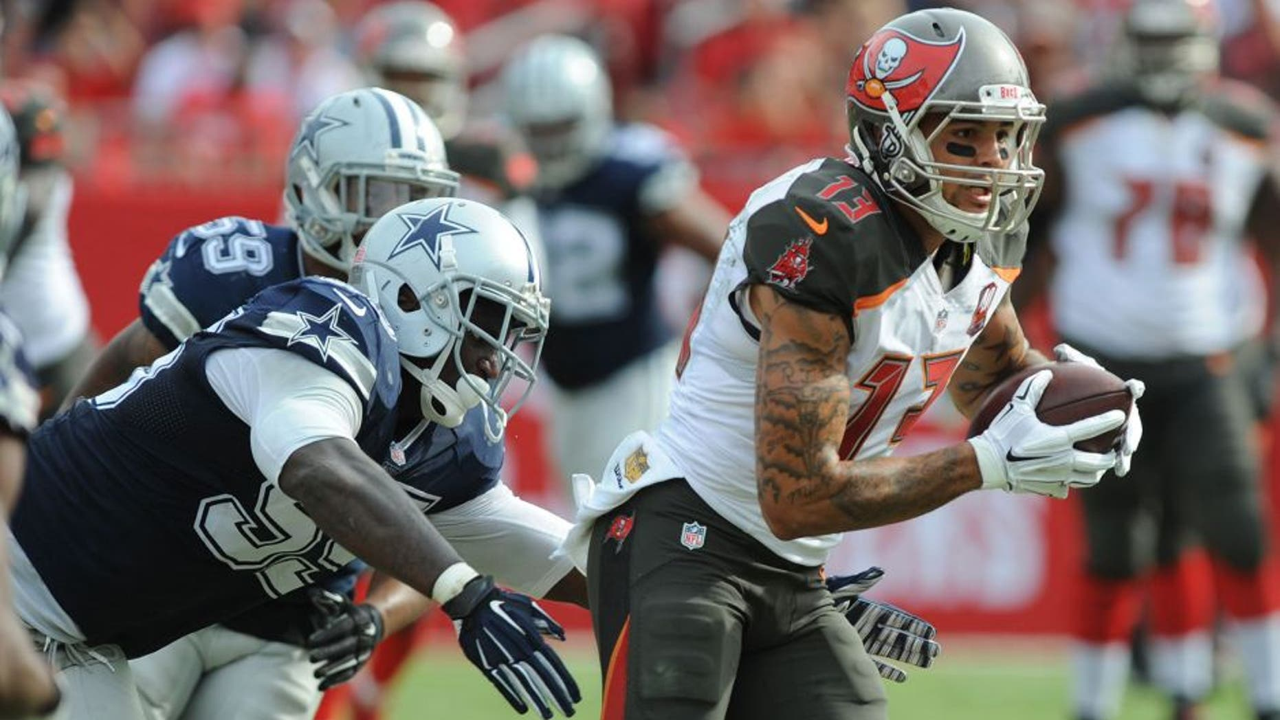 TAMPA, FL - NOVEMBER 15: Wide receiver Mike Evans #13 of the Tampa Bay Buccaneers runs after the catch past defensive tackle David Irving #95 of the Dallas Cowboys in the second quarter at Raymond James Stadium on November 15, 2015 in Tampa, Florida. (Photo by Cliff McBride/Getty Images)