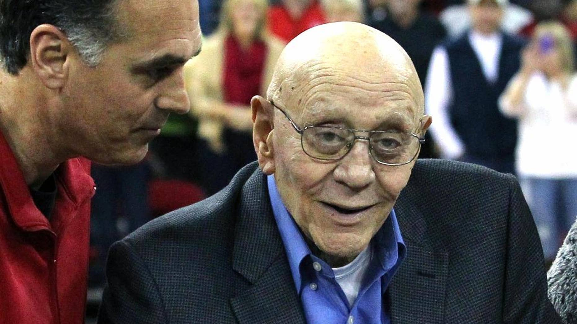 FILE - In this March 1, 2014, file photo, Jerry Tarkanian is escorted by his son, Danny, during halftime ceremonies honoring the former basketball coach at Fresno State University in Fresno, Calif. The Hall of Fame basketball coach is hospitalized in Las Vegas, where his son says he's being treated for pneumonia. (AP Photo/Gary Kazanjian, File)
