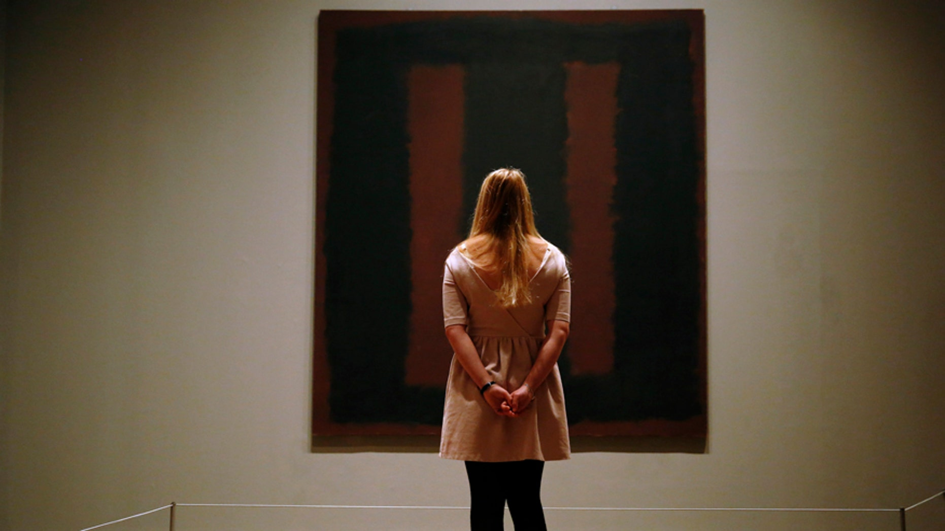 "A member of Tate staff poses with the restored Mark Rothko artwork ""Black on Maroon, 1958"" at the Tate Modern in London May 13, 2014. The picture was vandalised in 2012 by Polish man Wlodzimierz Umaniec - known also as Vladimir Umanets - who wrote ""Vladimir Umanets '12 A potential piece of yellowism"" on the canvas. He has since been given a jail sentence for the action. REUTERS/Luke MacGregor  (BRITAIN - Tags: CRIME LAW SOCIETY TPX IMAGES OF THE DAY) - RTR3OWAI"