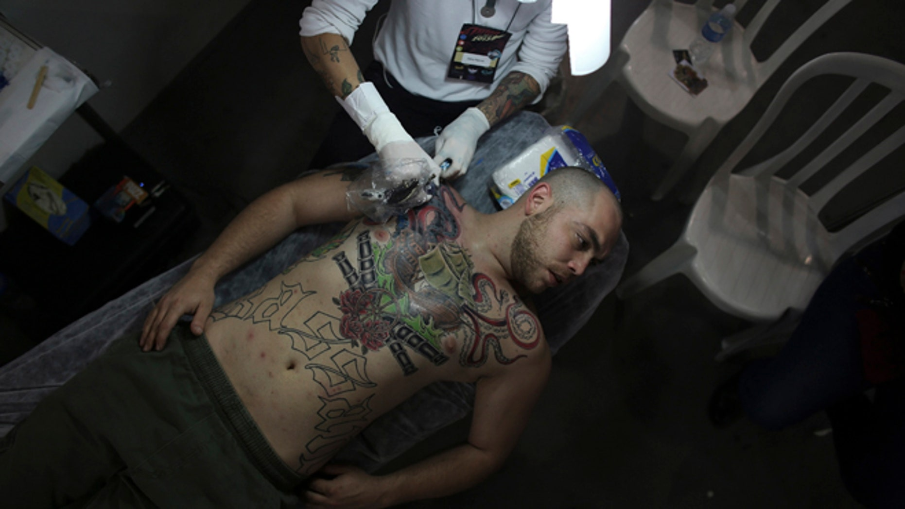 July 20, 2013: An artist works on a tattoo on the body of a man.