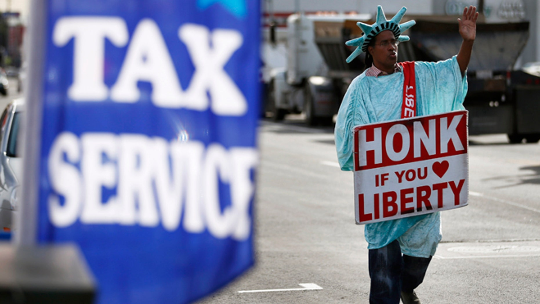 Jan. 22, 2013: Dressed as the Statue of Liberty, part-time employee, Zidkijah Zabad, waves to passing motorists while holding a sign to advertise for Liberty Tax Service in Los Angeles.