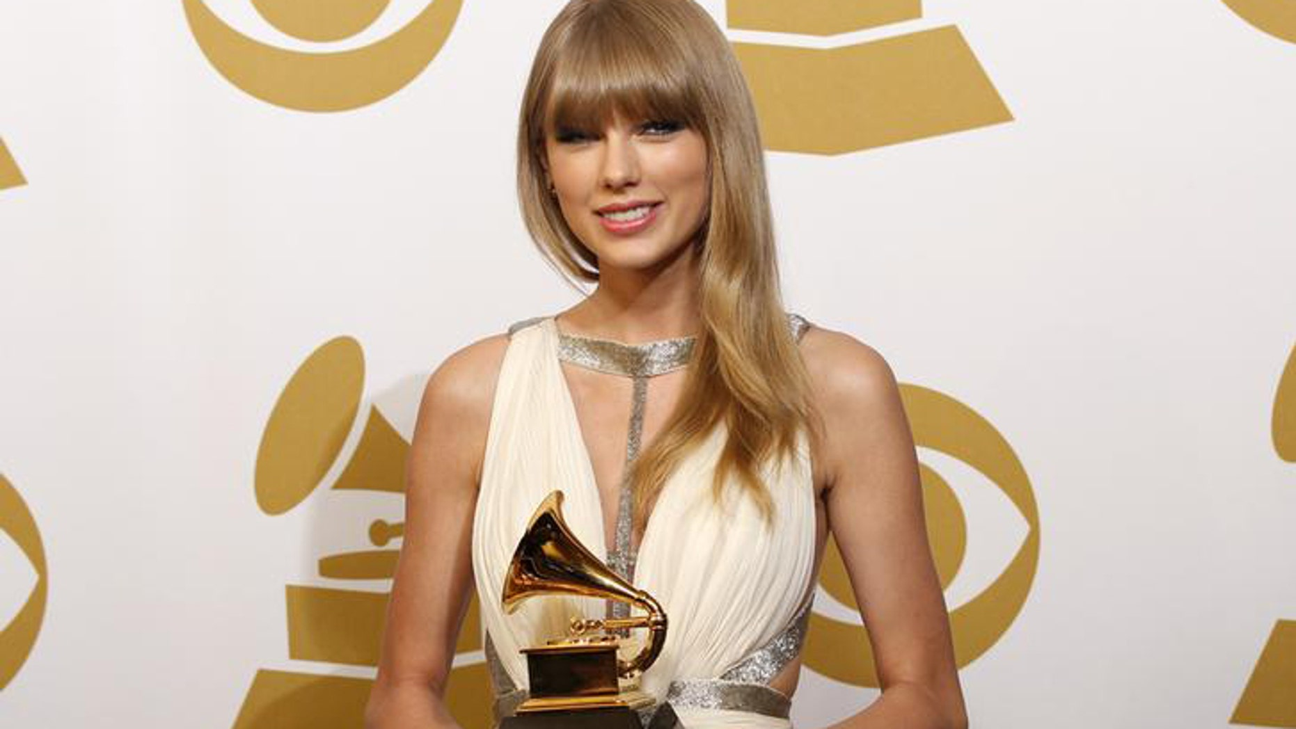 """Taylor Swift holds the award for Best Song Written For Visual Media for """"Safe & Sound"""" backstage at the 55th annual Grammy Awards in Los Angeles, California February 10, 2013.  REUTERS/Mario Anzuoni (UNITED STATES  - Tags: ENTERTAINMENT)  (GRAMMYS-BACKSTAGE)"""
