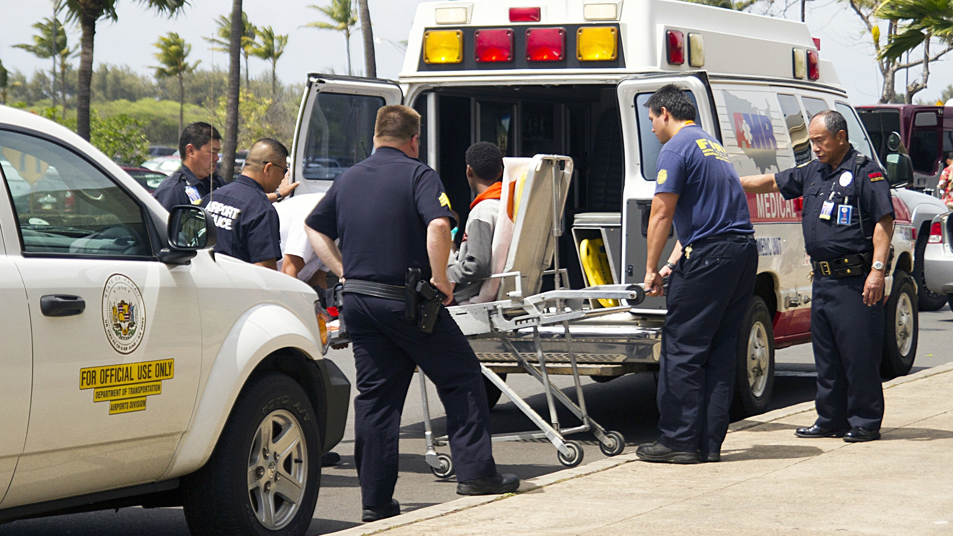 A 16-year-old boy, seen sitting on a stretcher center, who stowed away in the wheel well of a flight from San Jose, Calif., to Maui is loaded into an ambulance at Kahului Airport in Kahului, Maui, Hawaii Sunday afternoon, April 20, 2014.