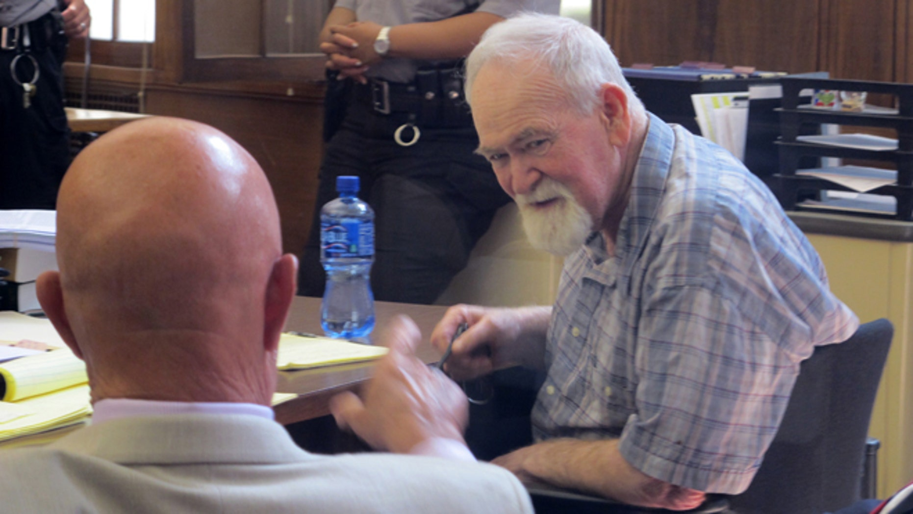 July 15: John Henry Spooner, 76, right, confers with his defense attorney in a Milwaukee courtroom.