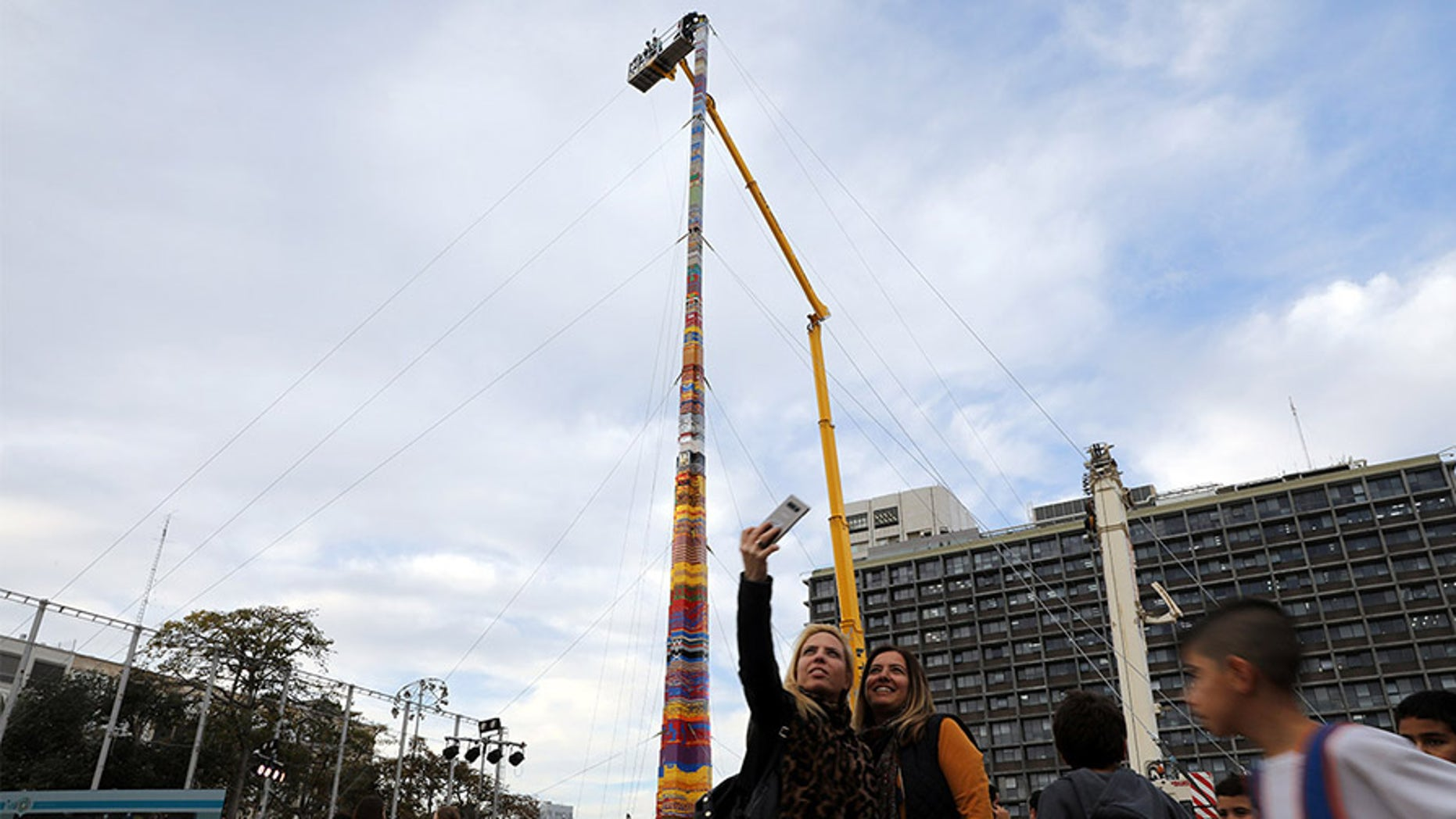 Women pose for a selfie next to a Lego tower that measures 118 feet.