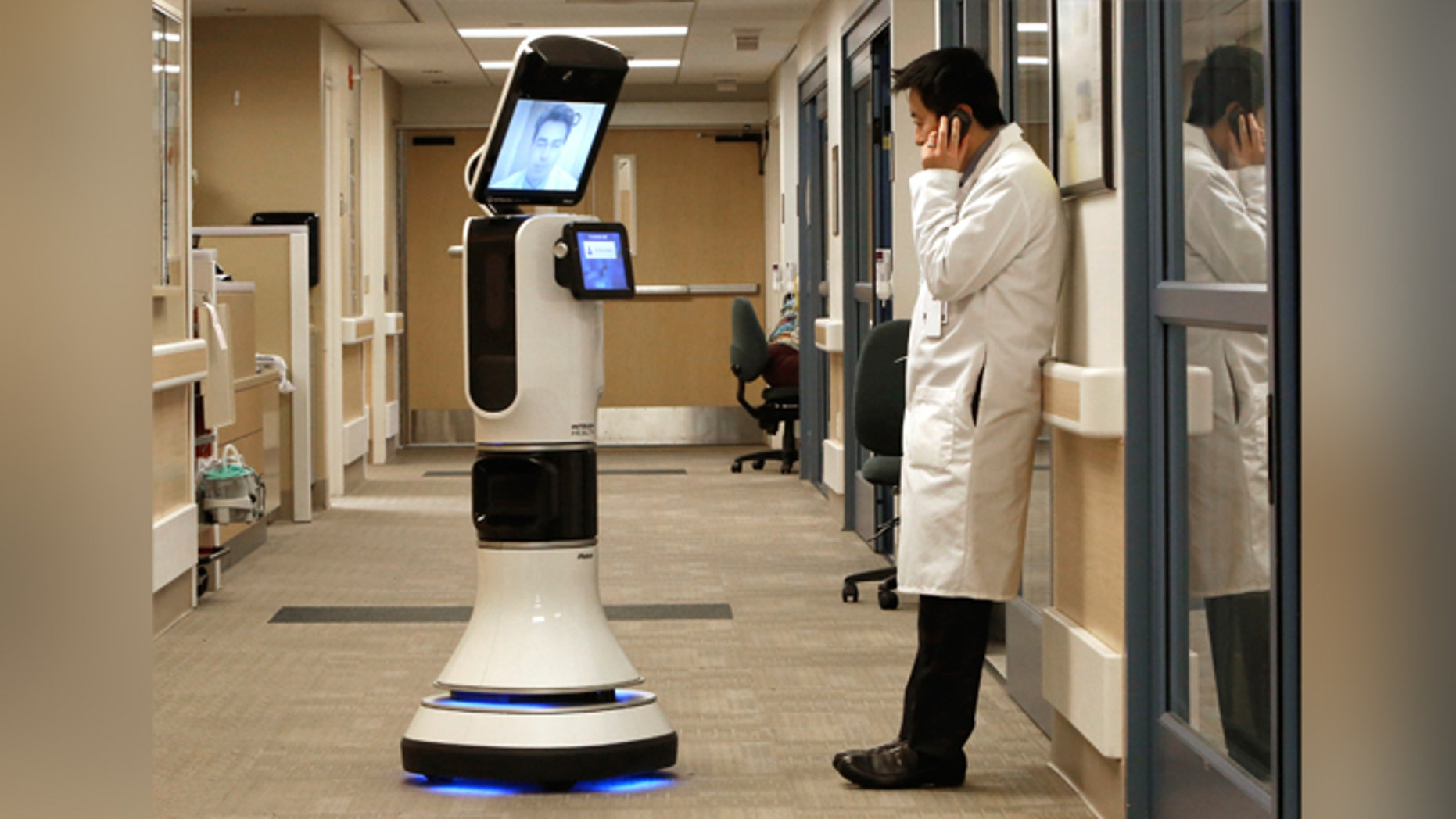 """Dr. Alan Shatzel, medical director of the Mercy Telehealth Network, is displayed on the monitor RP-VITA robot as he waits to confer with Dr. Alex Nee at Mercy San Juan Hospital in Carmichael, Calif. The robots enable physicians to have """"beam"""" themselves into hospitals to diagnose patients and offer medical advice during emergencies."""