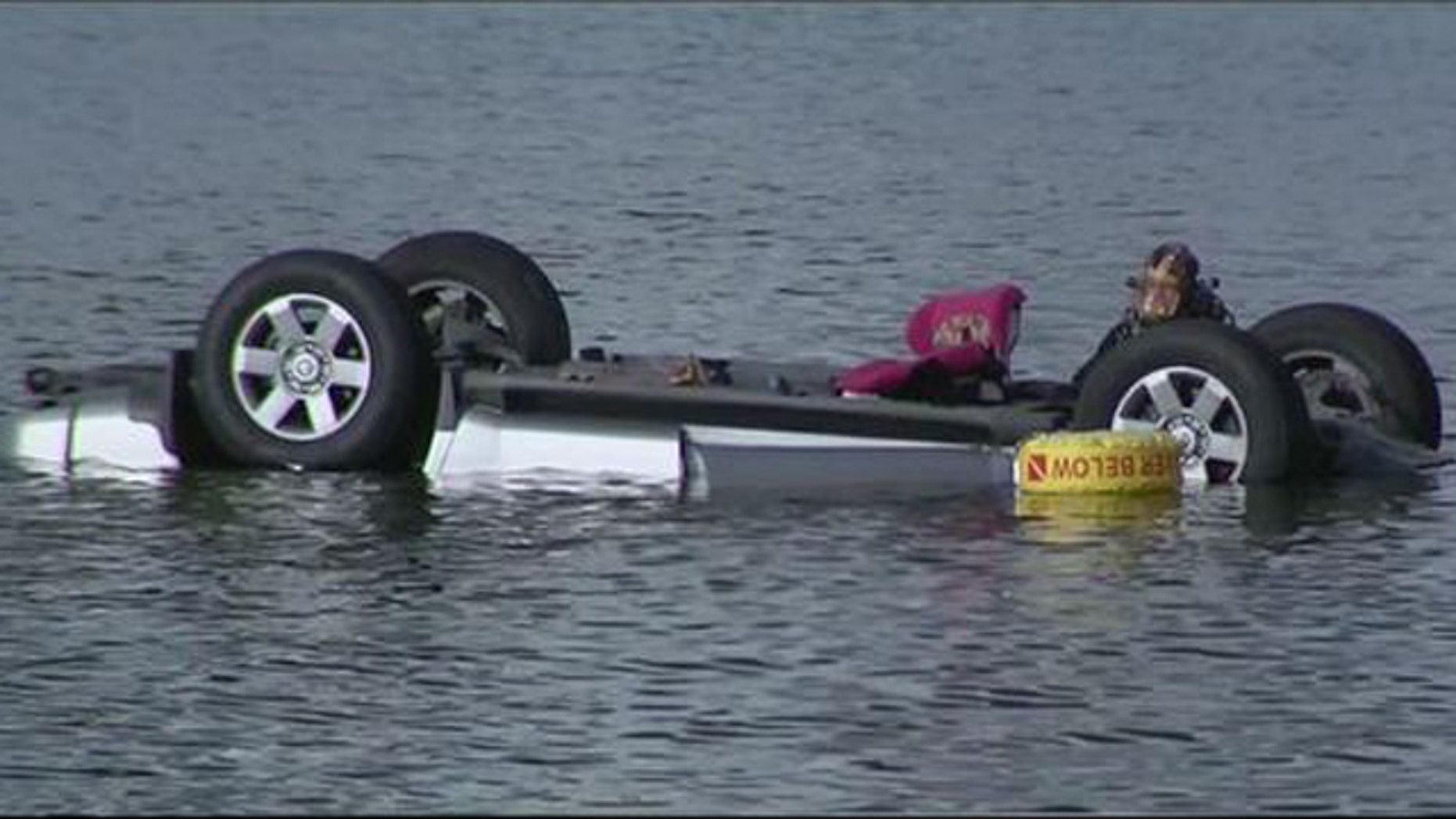 Oct. 18, 2015: A diver examines the SUV in Tempe Town Lake in Tempe, Ariz. Five people, including three children, died in the accident. (KSAZ)