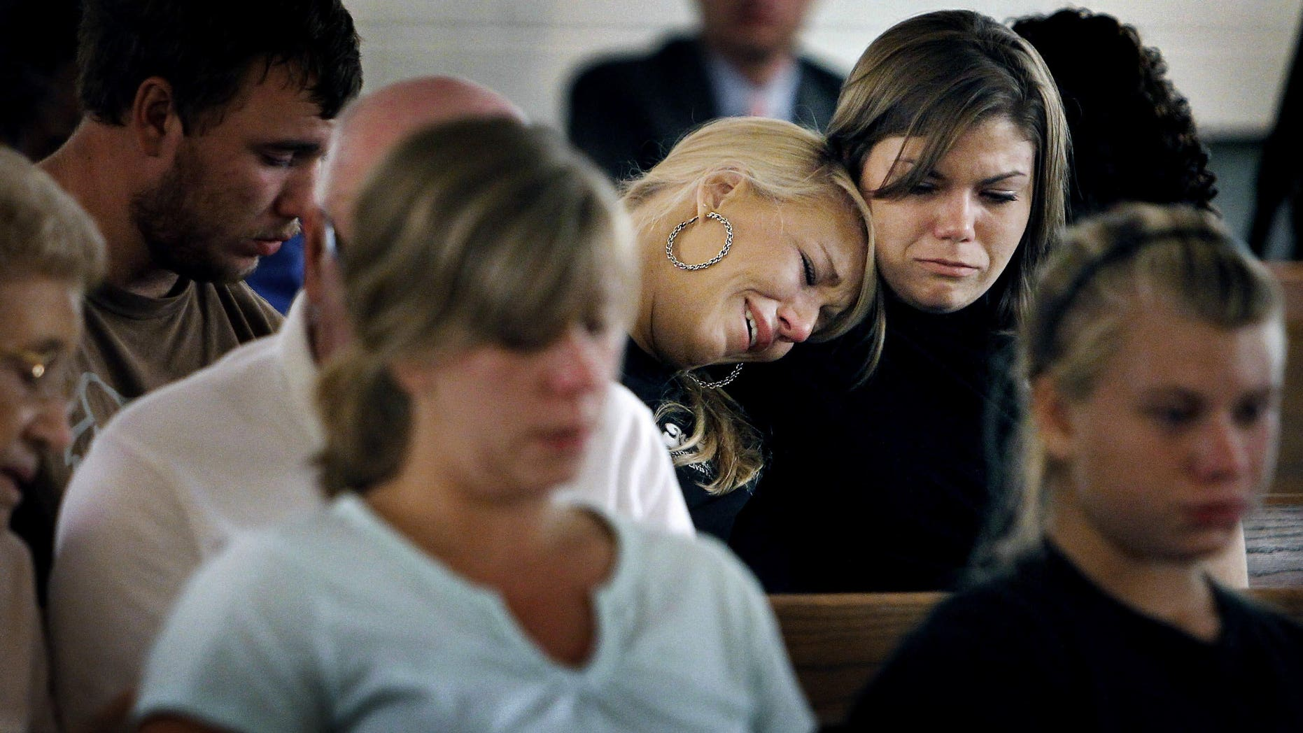 August 10: Sisters Brittany (left) and Kristen Bridges, both former students at Memphis Junior Academy, weep during an impromptu prayer vigil for slain principal Suzette York, who was killed in one of the school's classrooms in Memphis, Tennessee. The vigil held at Mullins United Methodist Church was attended by several former students and York family friends. Eduardo Marmolejo, a 17-year-old male student, has been charged with York's murder.