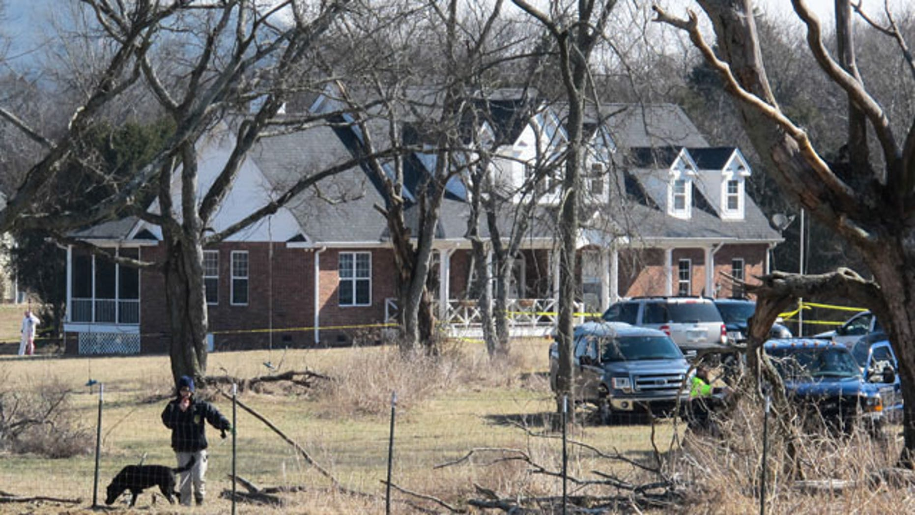 February 11, 2014: An officer and a dog inspect a fence near a home in Lebanon, Tenn. where police said a package exploded, killing a 74-year-old man and injuring a woman. (AP Photo/Lucas L. Johnson II)