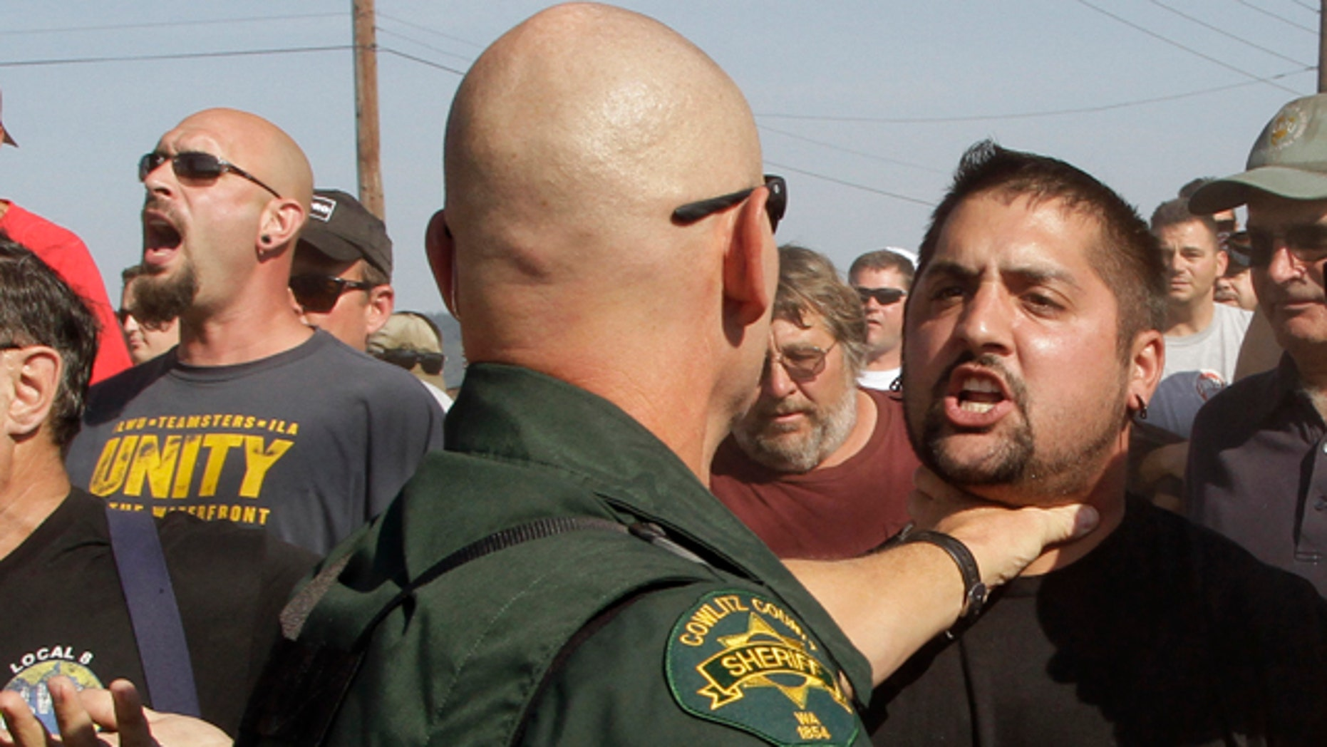 Sept. 7, 2011: A Cowlitz County Sheriff grabs a union worker by the throat as police move in on several hundred union workers blocking a grain train in Longview, Wash. Longshoremen blocked the train as part of an escalating dispute about labor at the EGT grain terminal at the Port of Longview.