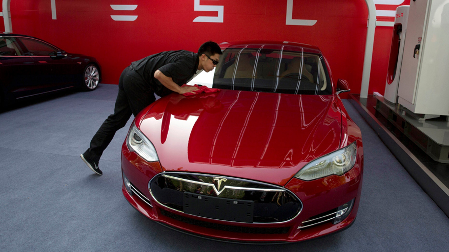 FILE - In this April 22, 2014 file photo, a worker cleans a Tesla Model S sedan before a event to deliver the first set of cars to customers in Beijing. Tesla Motors on Thursday, March 19, 2015 said it is updating its Model S electric car to help ease drivers' worries about running out of battery charge.  (AP Photo/Ng Han Guan, File)
