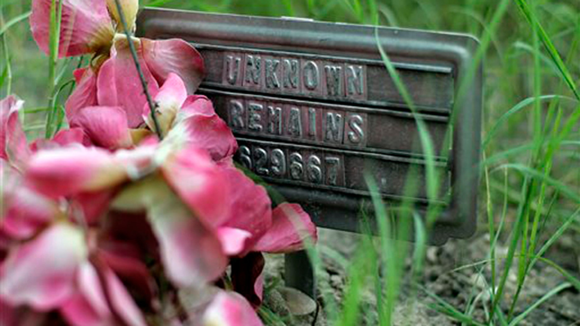 In this Aug. 23, 2013, photo, a small sign at a cemetery marks the grave site of an unidentified body found on a ranch, in Falfurrias, Texas. Brooks County, home to a Border Patrol checkpoint about an hour north of the border, handled 129 bodies last year of immigrants that died in their attempt to come to the U.S. Brooks County is now trying to improve its services by performing an autopsy on all immigrants and making greater efforts to identify them. (AP Photo/Eric Gay)