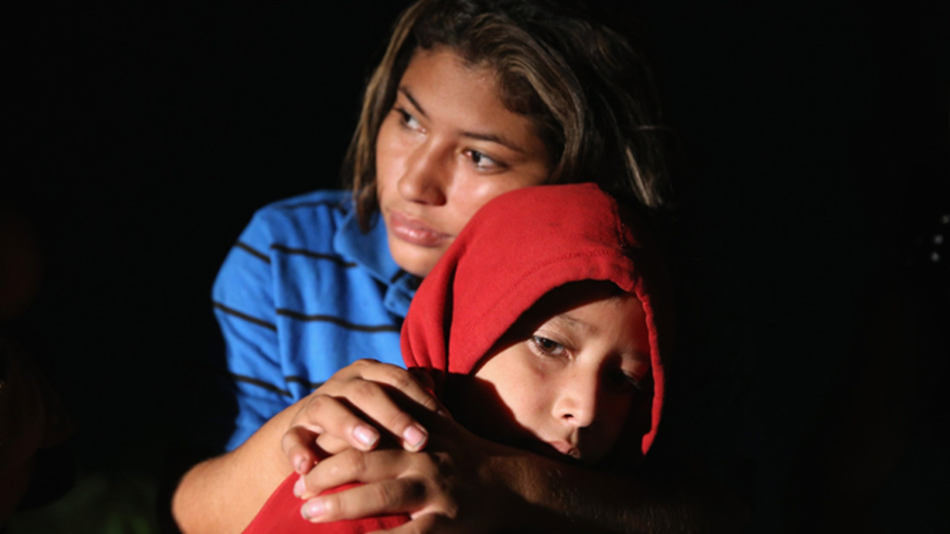 MISSION, TX - SEPTEMBER 08:  Families of Central American immigrants, including Lorena Arriaga, 27, and her son Jason Ramirez, 7, from El Salvador, turn themselves in to U.S. Border Patrol agents after crossing the Rio Grande River from Mexico on September 8, 2014 to Mission, Texas. Although the numbers of such immigrant families and unaccompanied minors have decreased from a springtime high, thousands continue to cross in the border illegally into the United States. Texas' Rio Grande Valley sector is the busiest area for illegal border crossings, especially for Central Americans, into the U.S.  (Photo by John Moore/Getty Images)