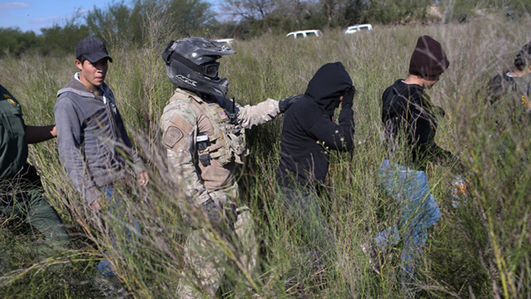 A Border Patrol agent leads undocumented immigrants on December 7, 2015 near Rio Grande City, Texas.