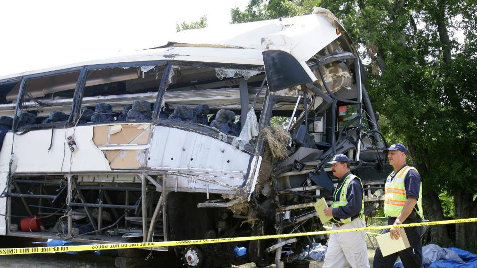 FILE - National Transportation Safety Board investigators David Rayburn, left, and Robert Accetta walk in this Aug. 10, 2008 file photo past a charter bus involved in a deadly accident early Friday that killed 17 people and left at least eight others in critical condition in Sherman, Texas. The owner of the Houston bus company who was charged after a 2008 crash has avoided prison after a federal judge sentenced him to three years of probation in a plea agreement Friday Oct. 24, 2014.  (AP Photo/Matt Slocum, File)