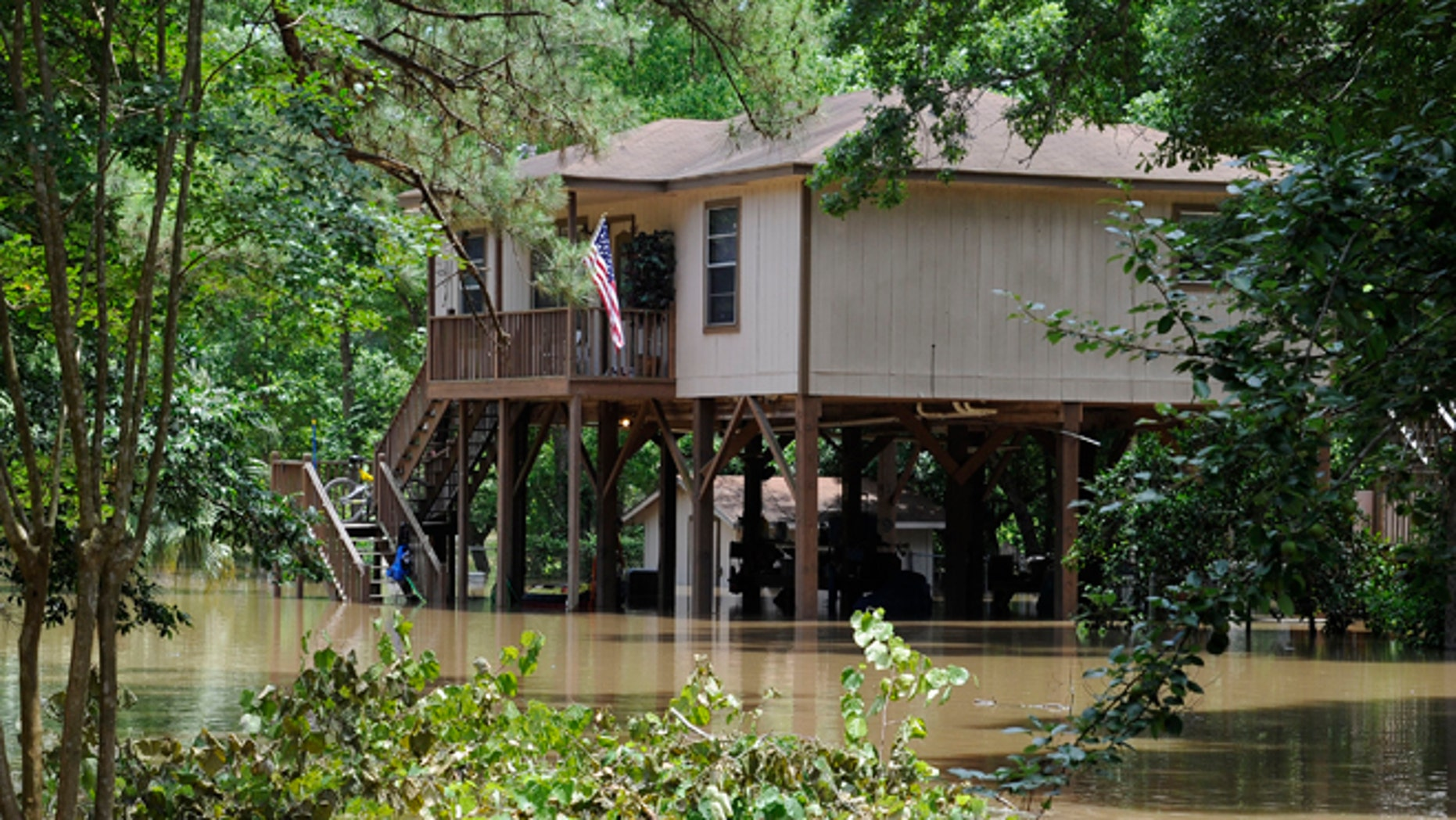 A house built on tall piers is surrounded by flood water from the San Jacinto River Thursday, May 28, 2015, in Kingwood, Texas. Although the deadly thunderstorms that lashed much of Texas have tapered off, many cities were still in danger of flooding Thursday as heavy rain from earlier in the week poured downstream, swelling rivers.  (AP Photo/Pat Sullivan)