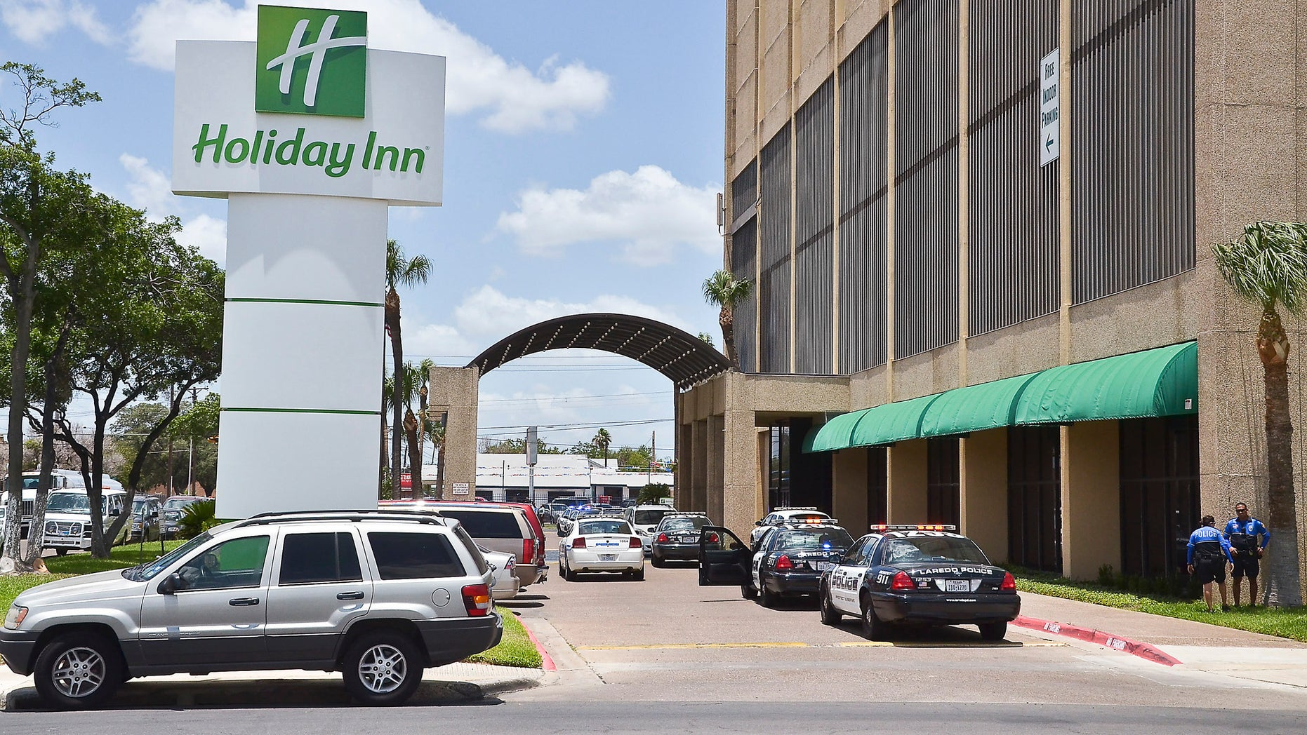June 19, 2012: A line of Laredo Police Department vehicles line the entrance to the Holiday Inn Civic Center in Laredo, Texas, where two young boys were shot.