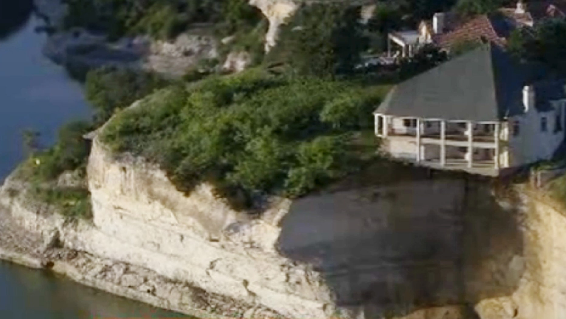 June 10, 2014: In this image taken from video provided by WFAA-TV, a luxury house teeters on a cliff about 75 feet above Lake Whitney in Whitney, Texas.