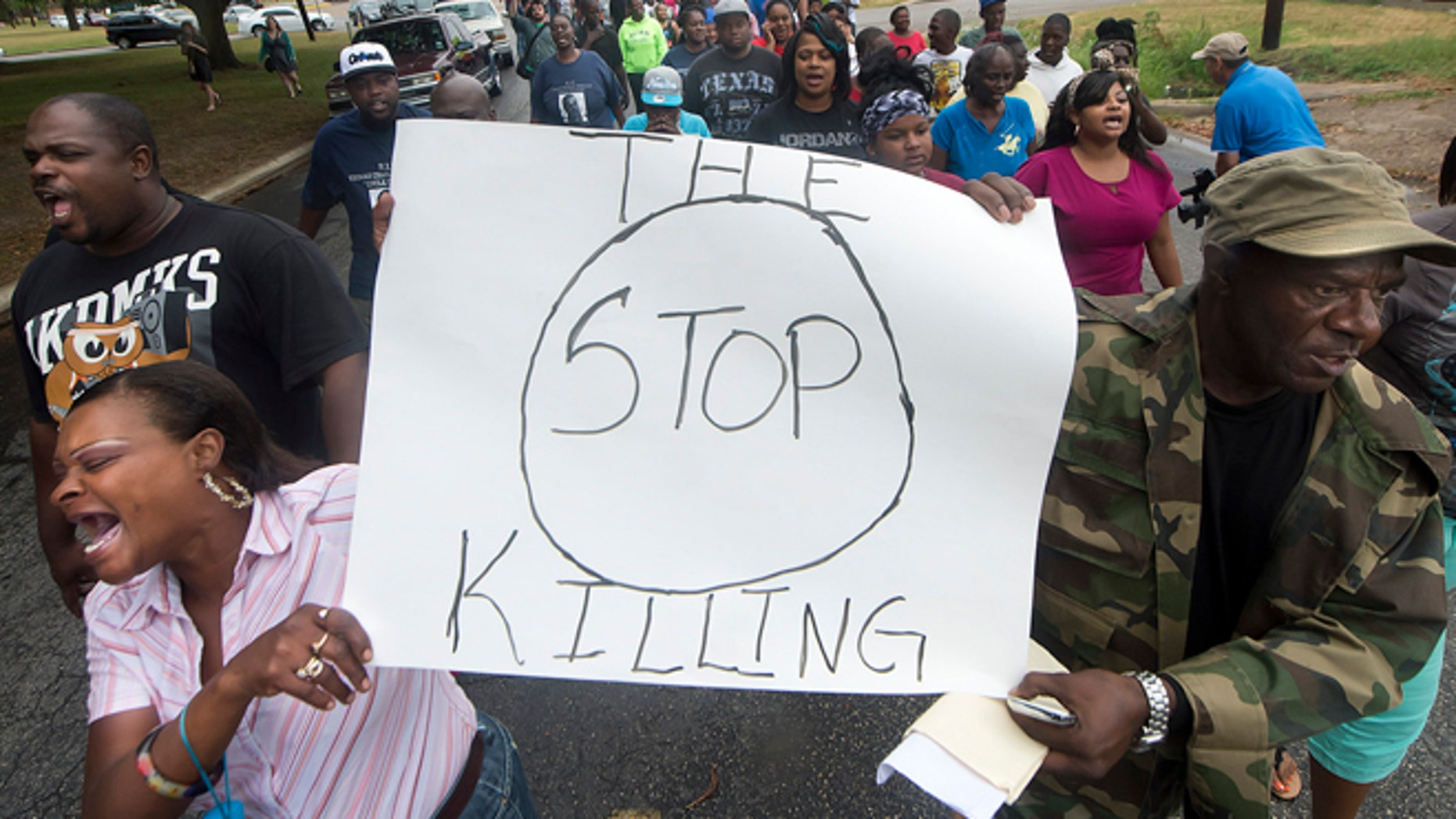 """K.K. Davis, left, and Tommy Jones of Hearne carry a sign with other protesters outside the Hearne, Texas police department Thursday, May 8, 2014 following the Tuesday shooting of 93-year-old woman. Robertson County District Attorney Coty Siegert said Pearlie Golden was shot Tuesday night by Officer Stephen Stem. Stem was responding to a 911 call about a disturbance involving a woman with a gun. The Hearne Police Department says Golden """"brandished a firearm"""" when Stem encountered her. He then shot her multiple times. The investigation into the shooting is being handled by the Texas Rangers.  (AP Photo/Bryan College Station Eagle, Stuart Villanueva)"""