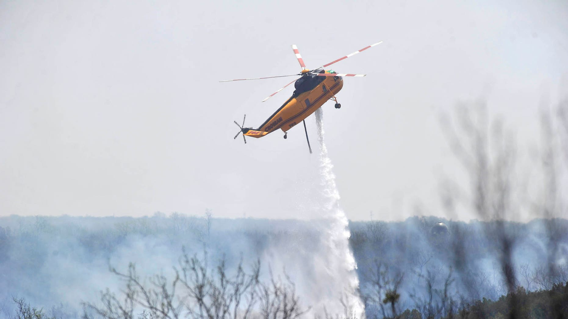 April 8: A Texas Forest Service helicopter drops water on a wildfire burning east of Highway 83 in Texas' northern Stonewall County. (AP Photo/The Abilene Reporter-News)