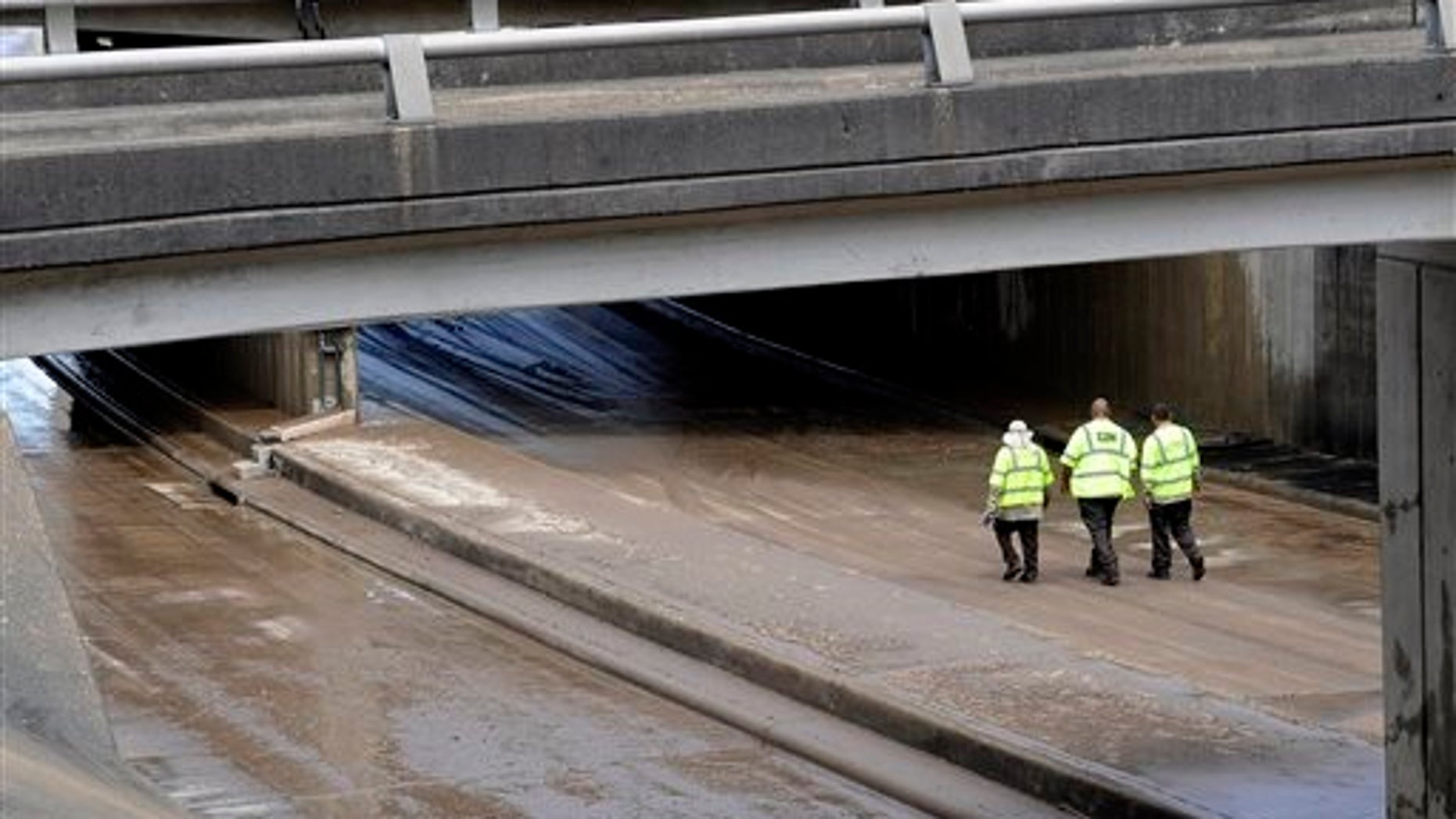 City of Houston workers walk along a wet, muddy, low stretch of Allen Parkway near downtown Houston, Wednesday, May 27, 2015. Heavy rains and flooding have kept the section closed to traffic. (AP Photo/Pat Sullivan)
