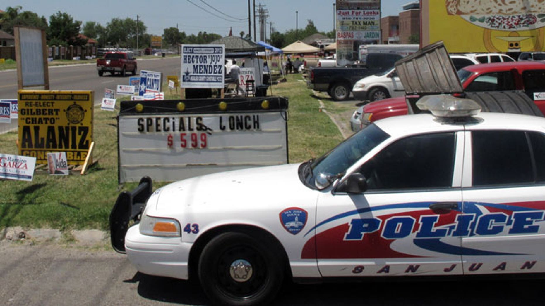 May 29, 2012: Police remain on a busy corner in San Juan, Texas where one man holding a campaign sign was shot in the leg by someone in a passing vehicle.