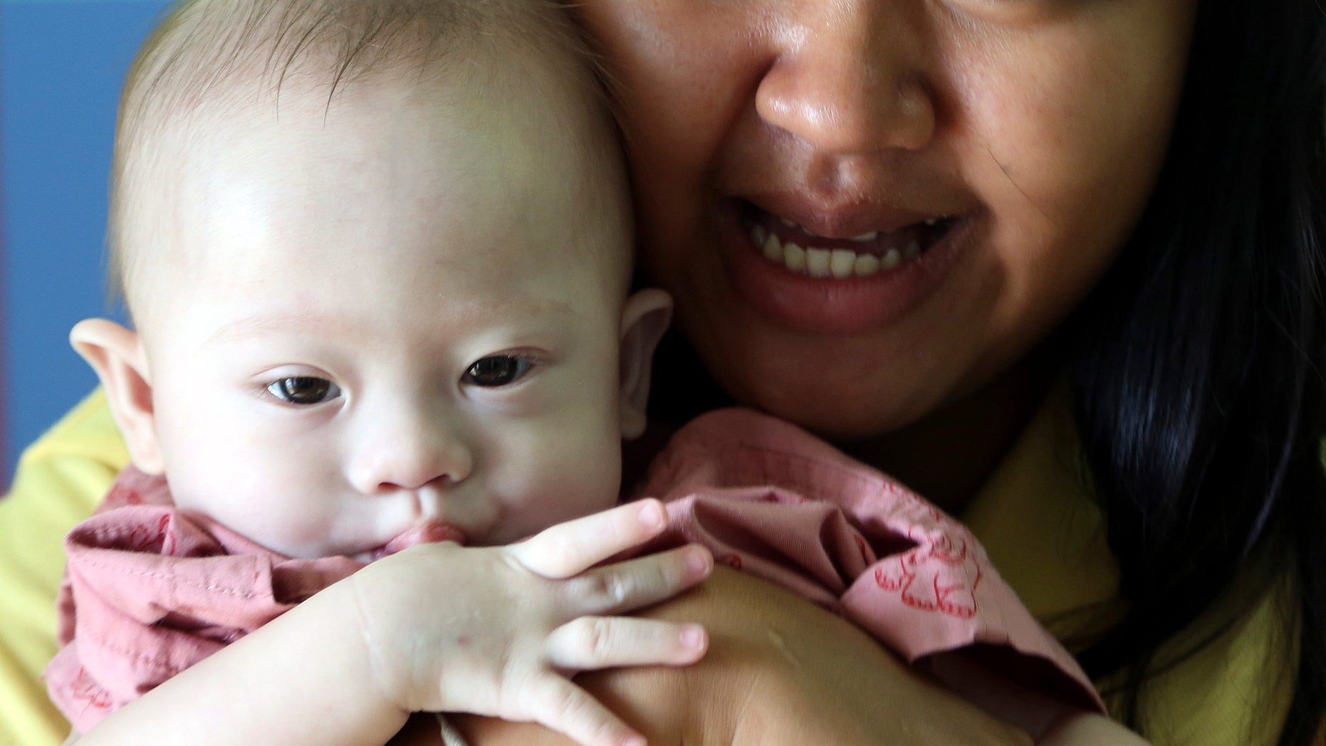 Aug. 3, 2014 - Thai surrogate mother Pattaramon Chanbua, 21, with Gammy, a 9-month old boy born with Down syndrome, at a hospital in Chonburi province, southeastern Thailand. The case of an Australian couple accused of abandoning their baby after discovering he had Down syndrome, has shined light on the unregulated business of commercial surrogacy.